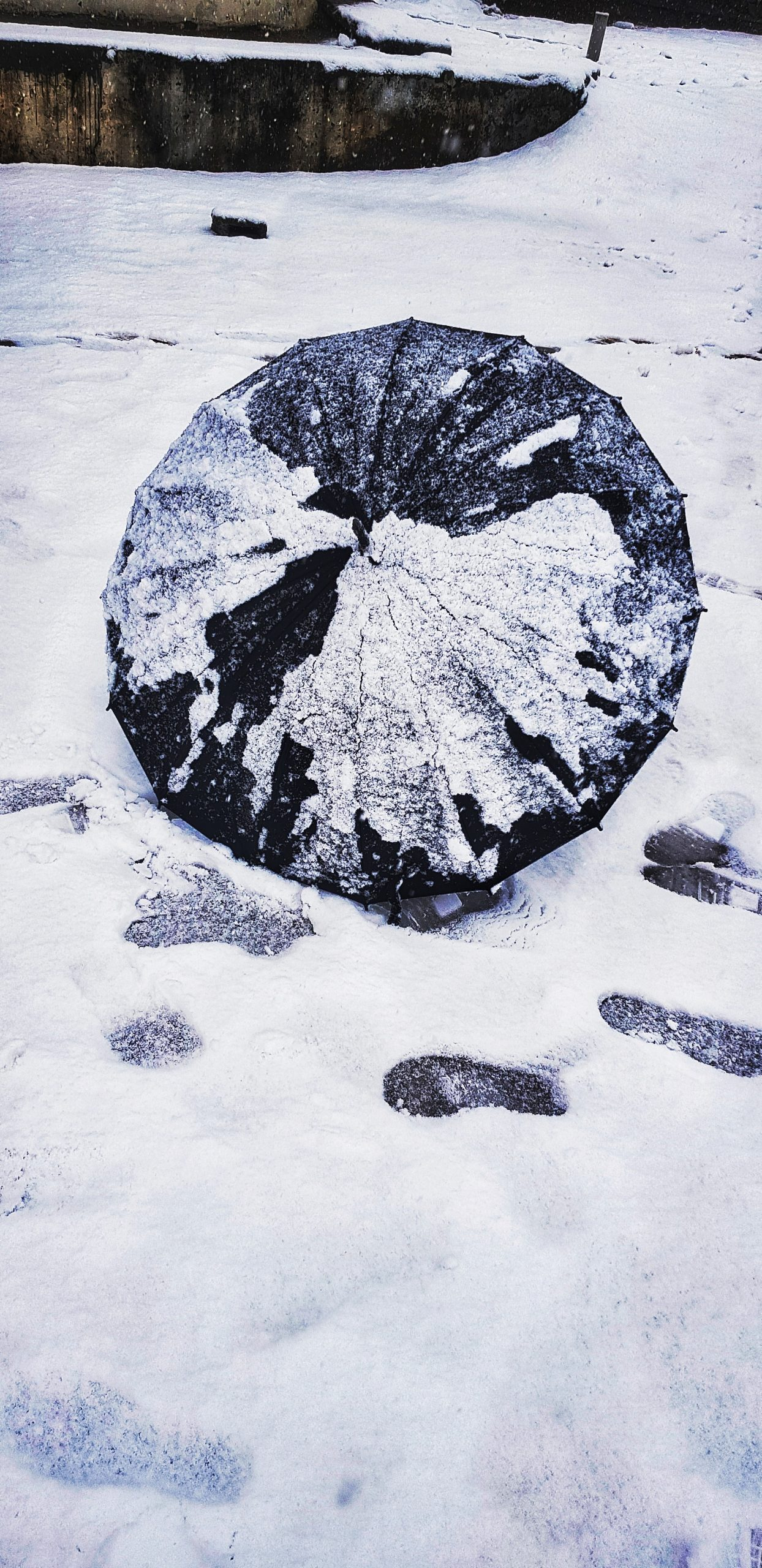 Black umbrella and footsteps in the snow.