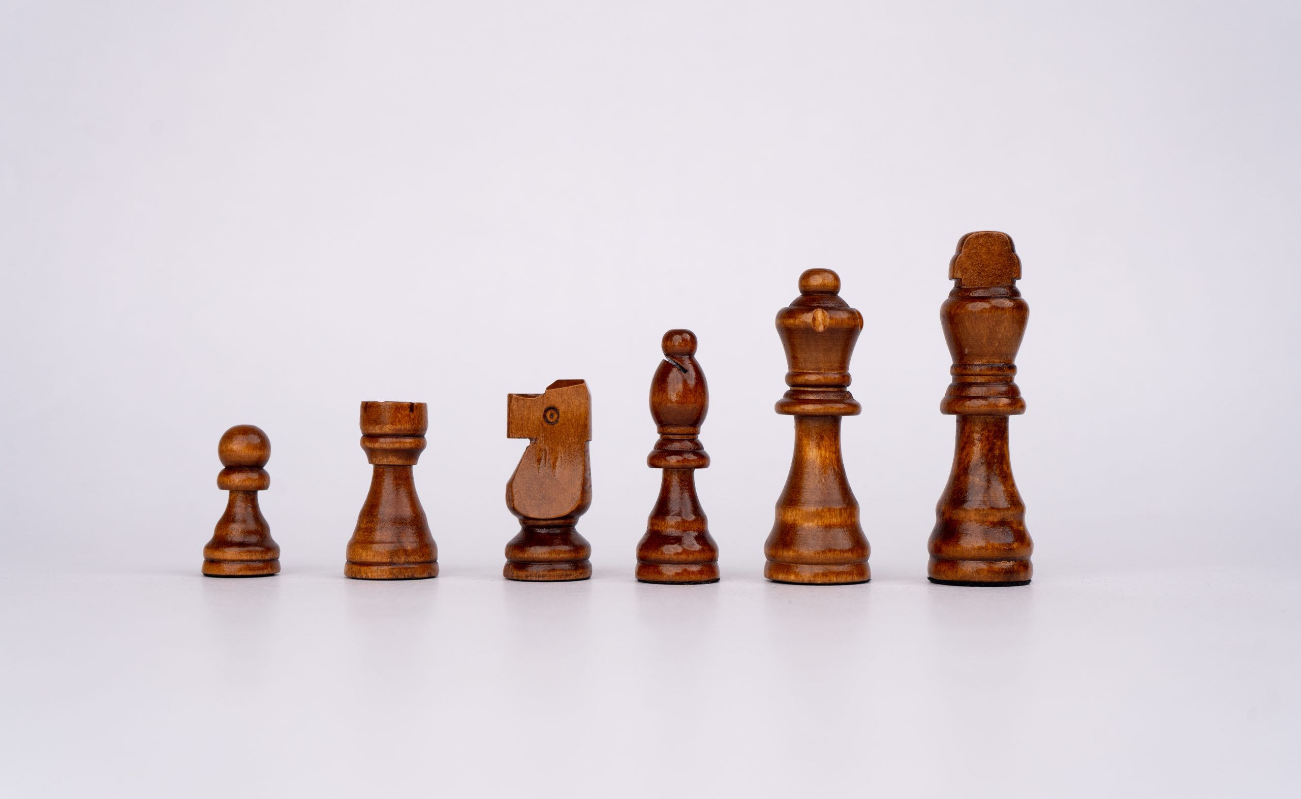 Black wooden chess pieces in formation