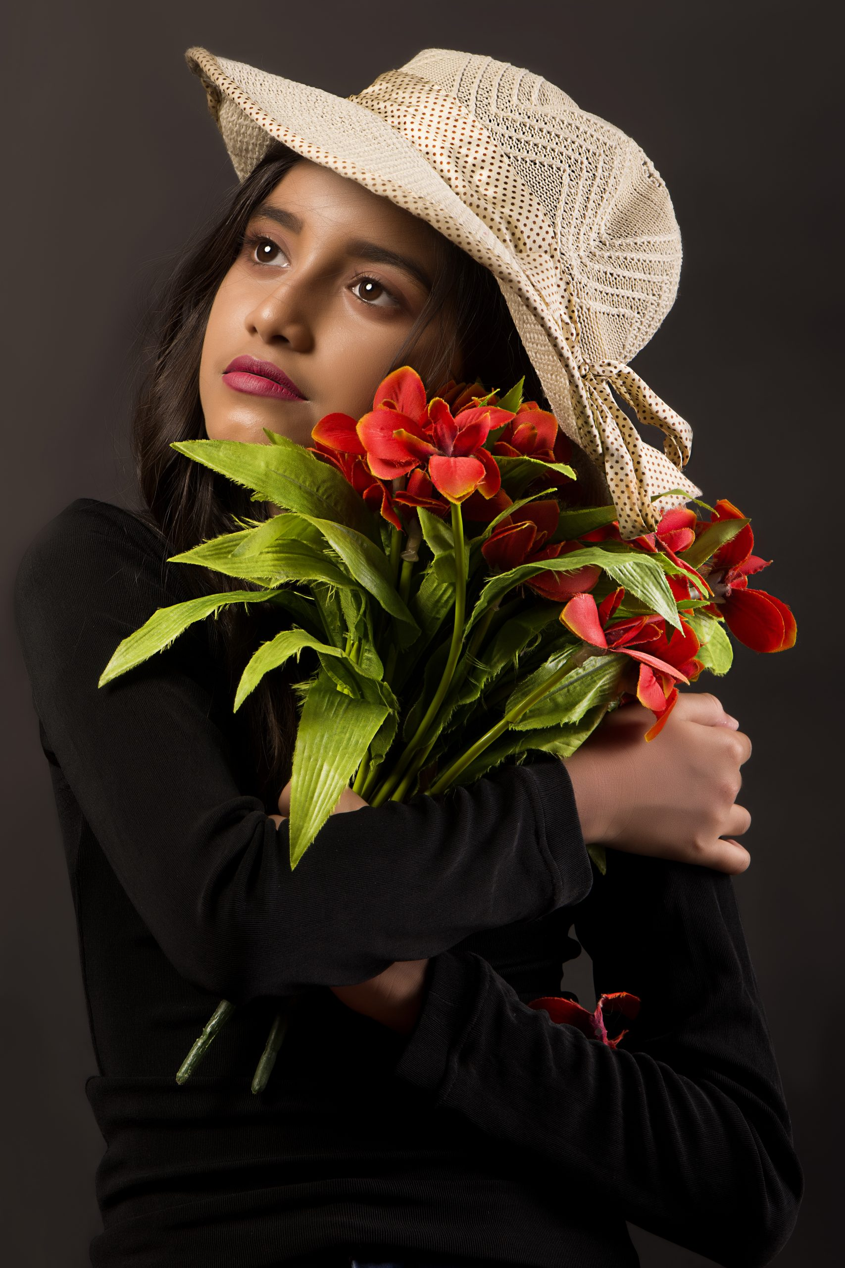 A girl posing for photograph with flowers in her hands.