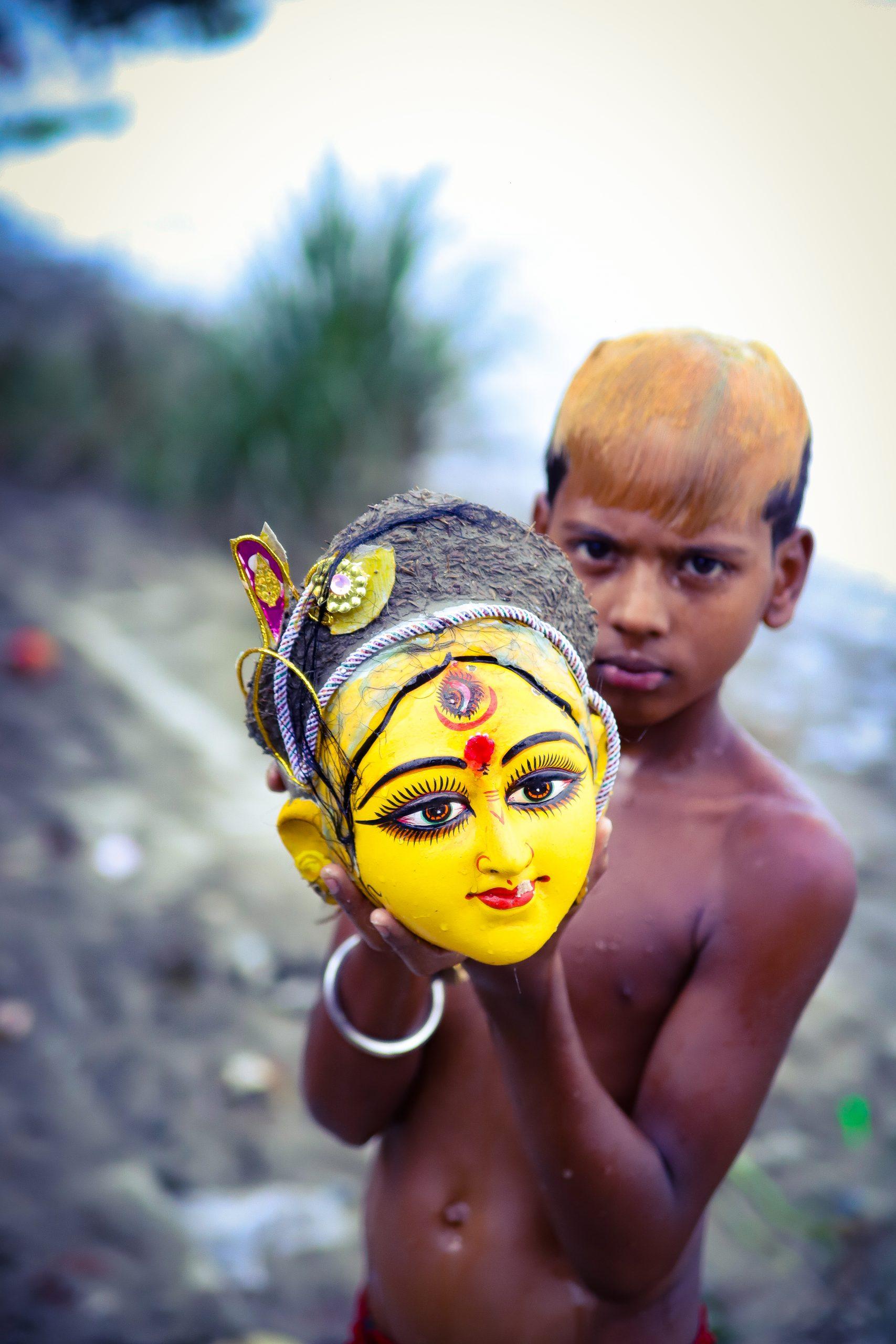 Boy holding Durga idol during Durga Puja festival in Kolkata