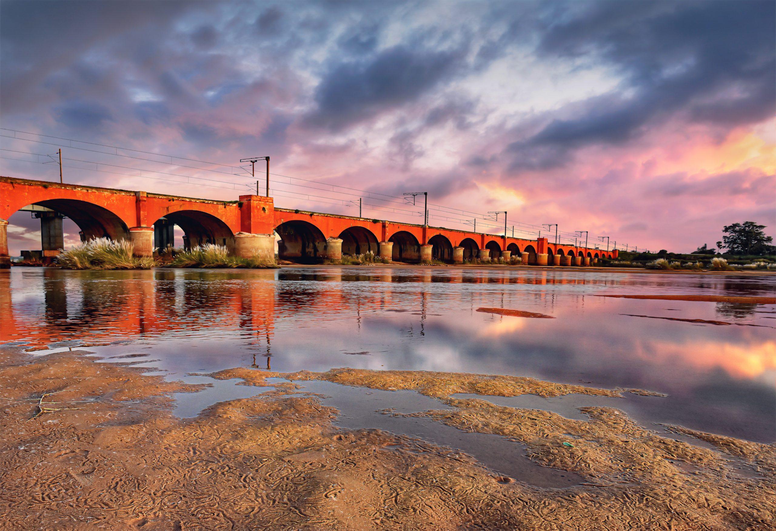 Clouds over a red bridge