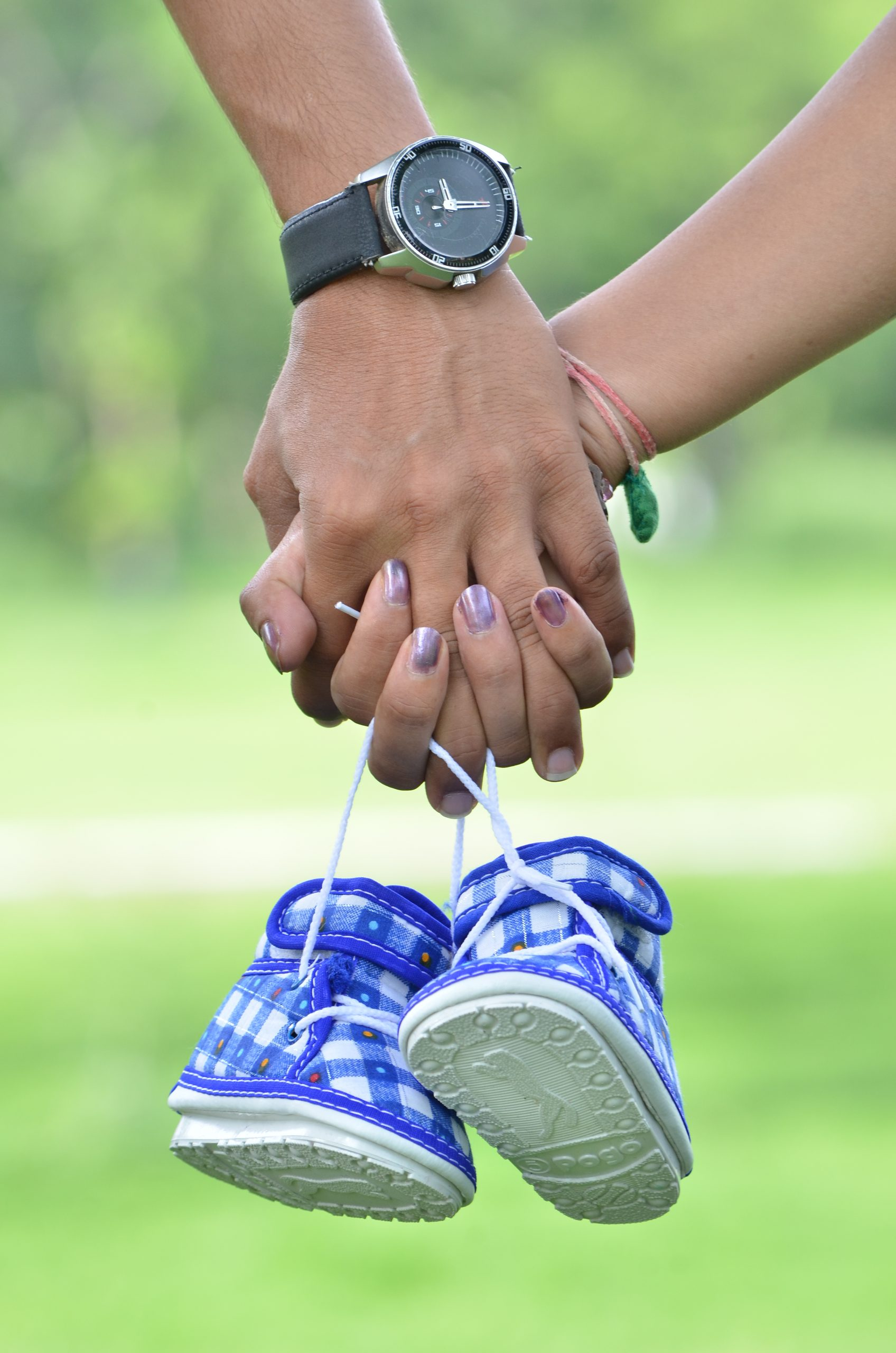 Couple holding hands and a pair of baby shoes