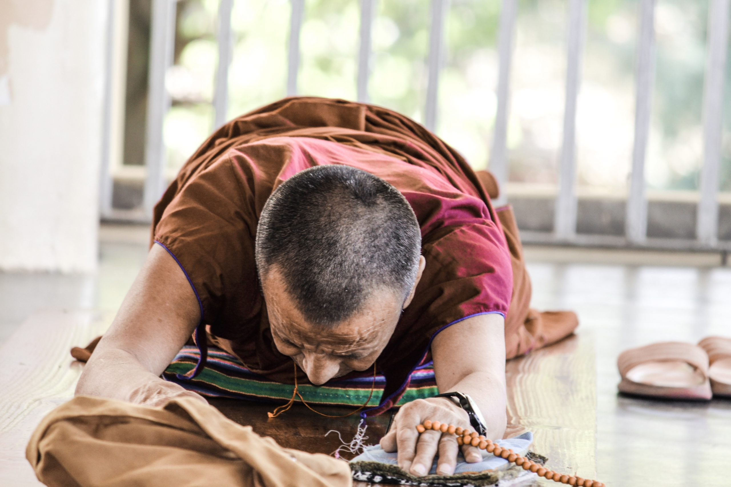 Monk kneeling to Buddha.