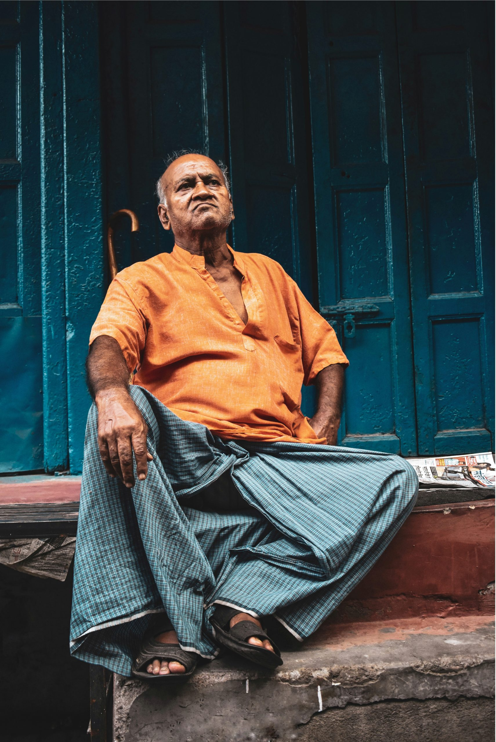 An Indian man sitting angrily on the steps.
