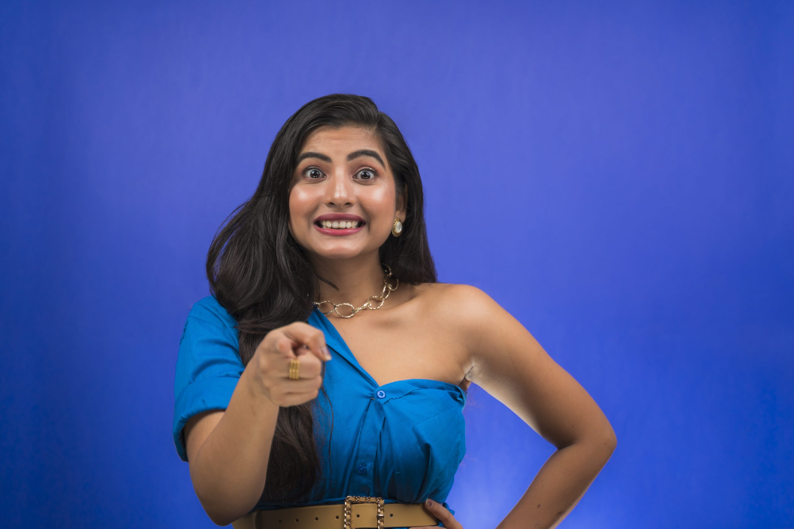 Excited indian girl pointing towards camera