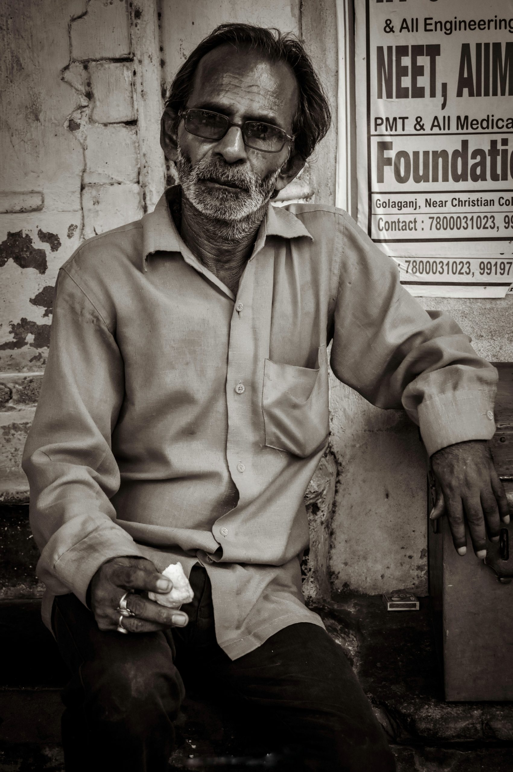 An old man sitting on a bench.