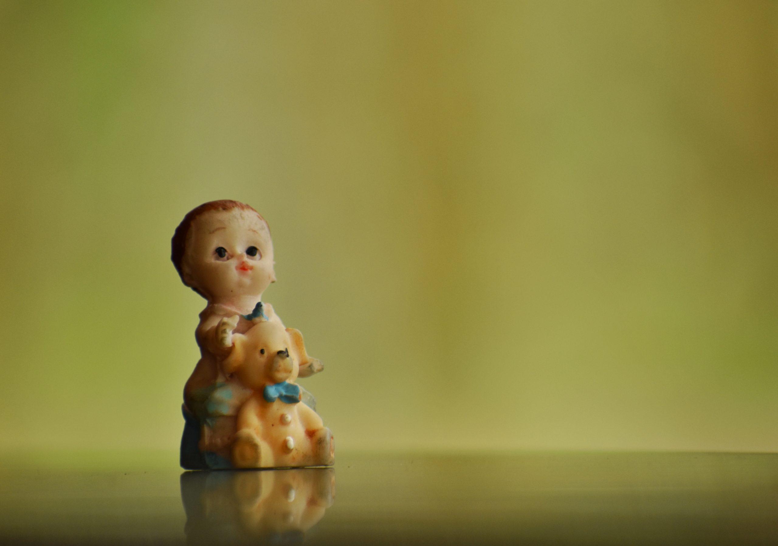 Figurine of boy holding teddy bear