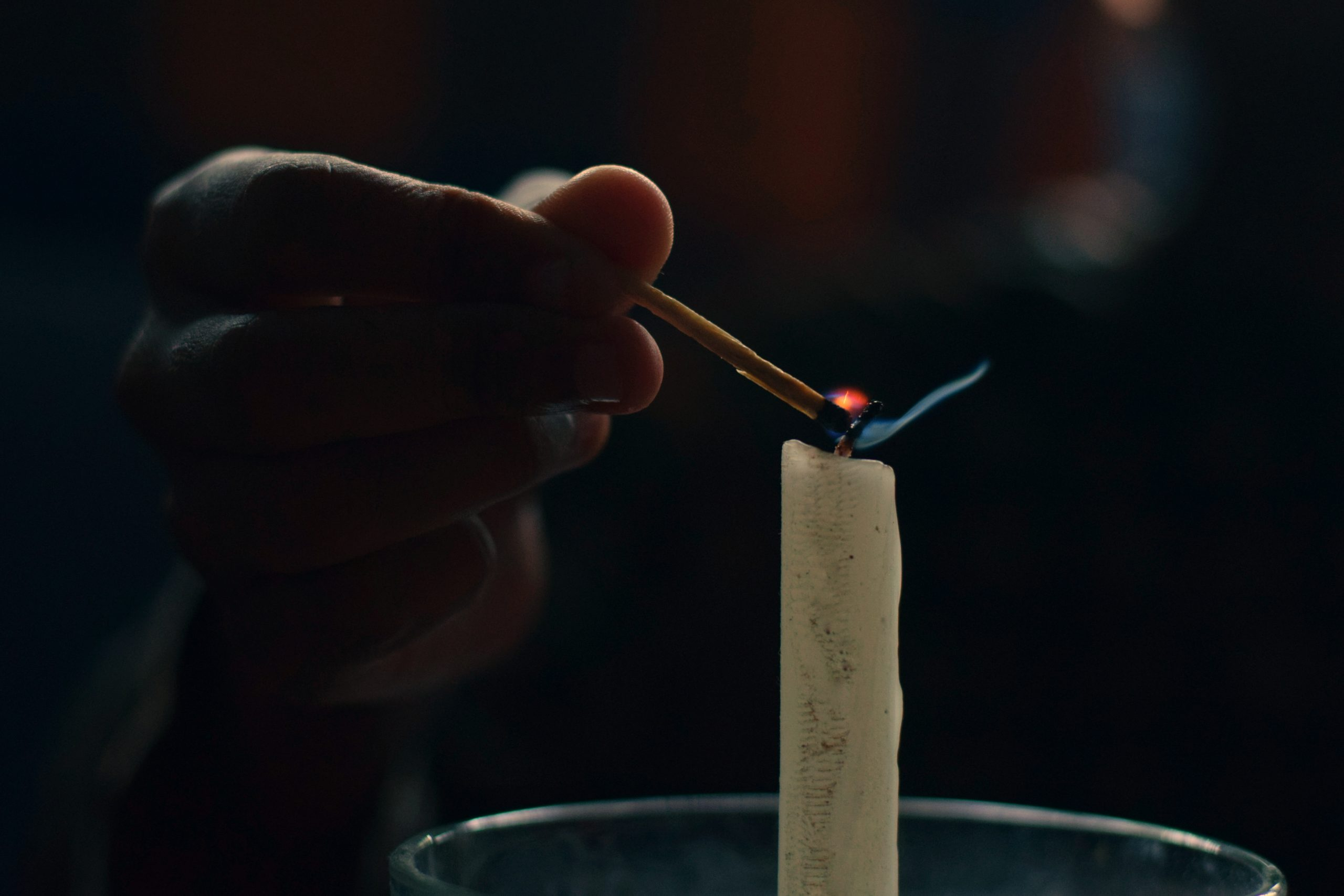 Hand Lighting a Candle on Focus