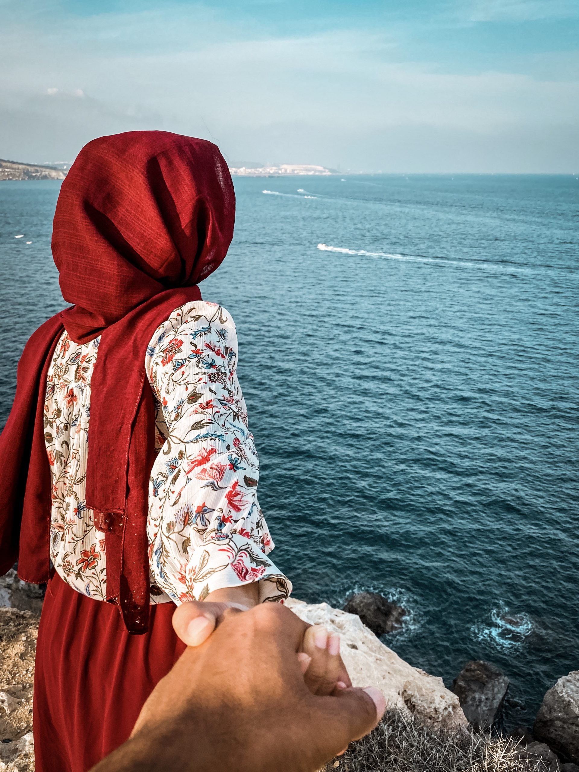 Girl Holding her Partner Against the Sea on a Cliff
