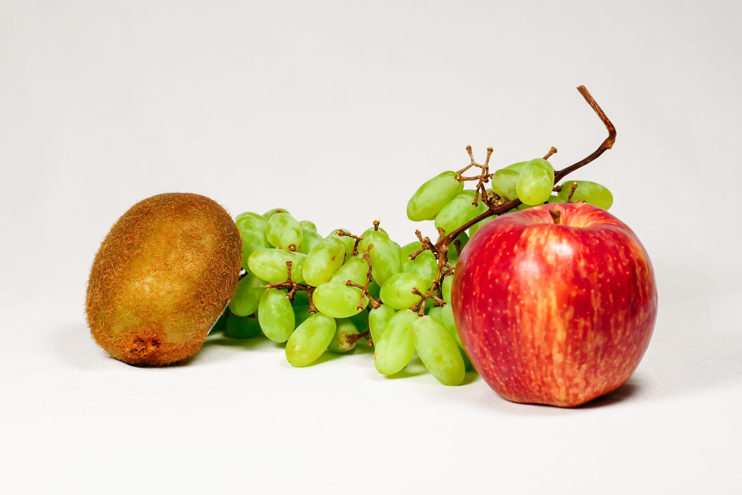 Grapes, kiwi and apple in white background