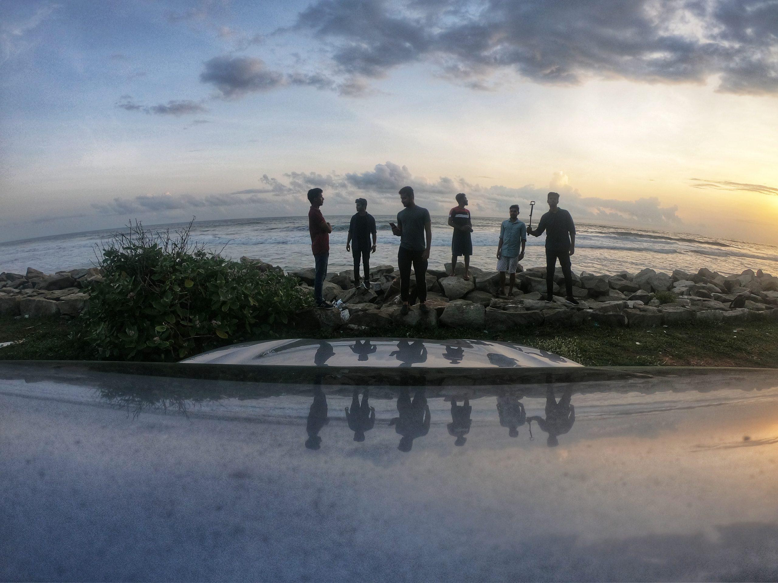 Group of men standing on rocks beside the sea