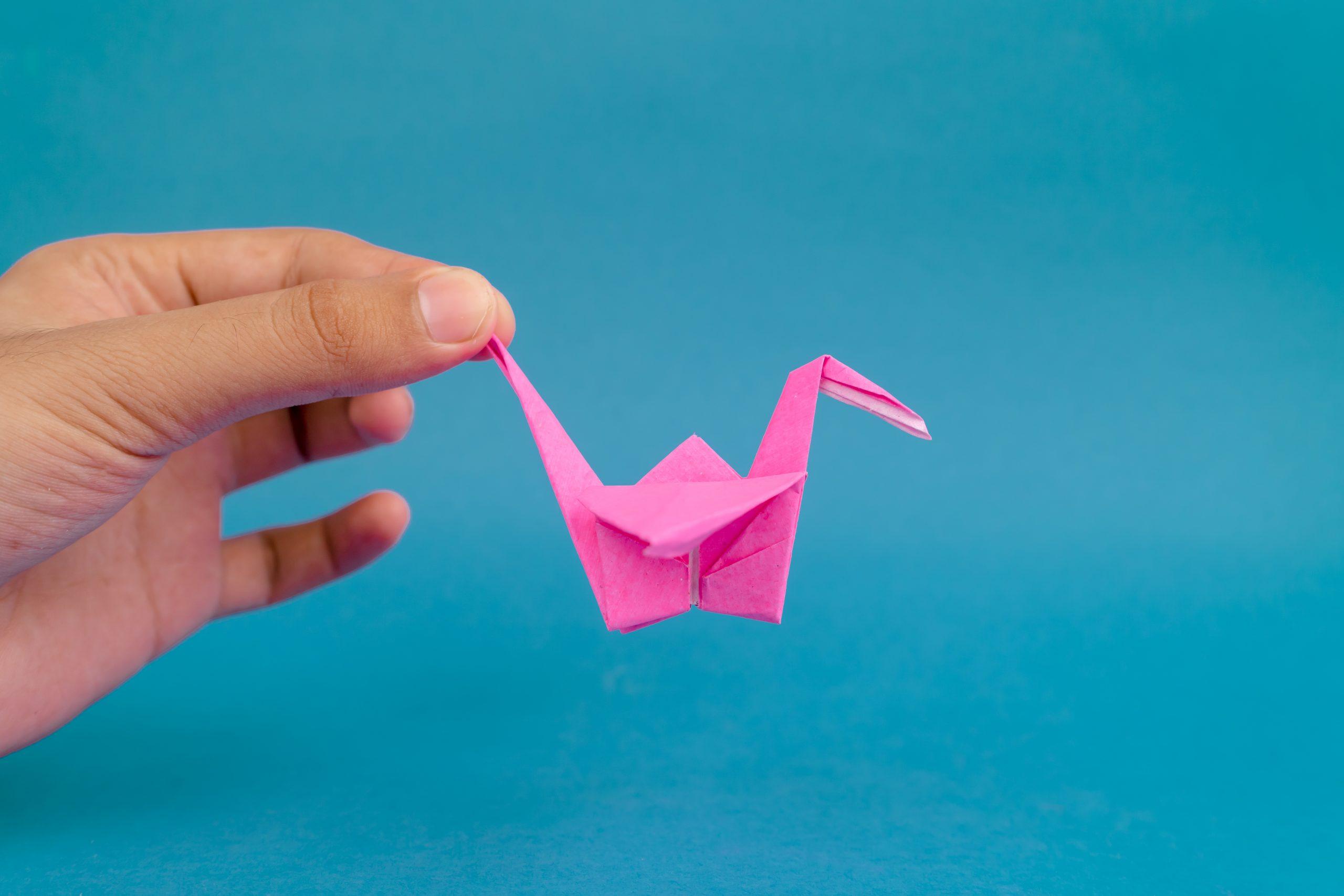 Hand holding pink crane origami