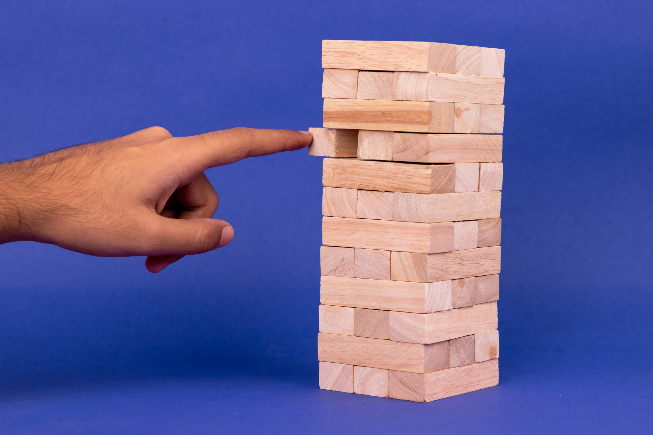 Hand sliding a piece of jenga