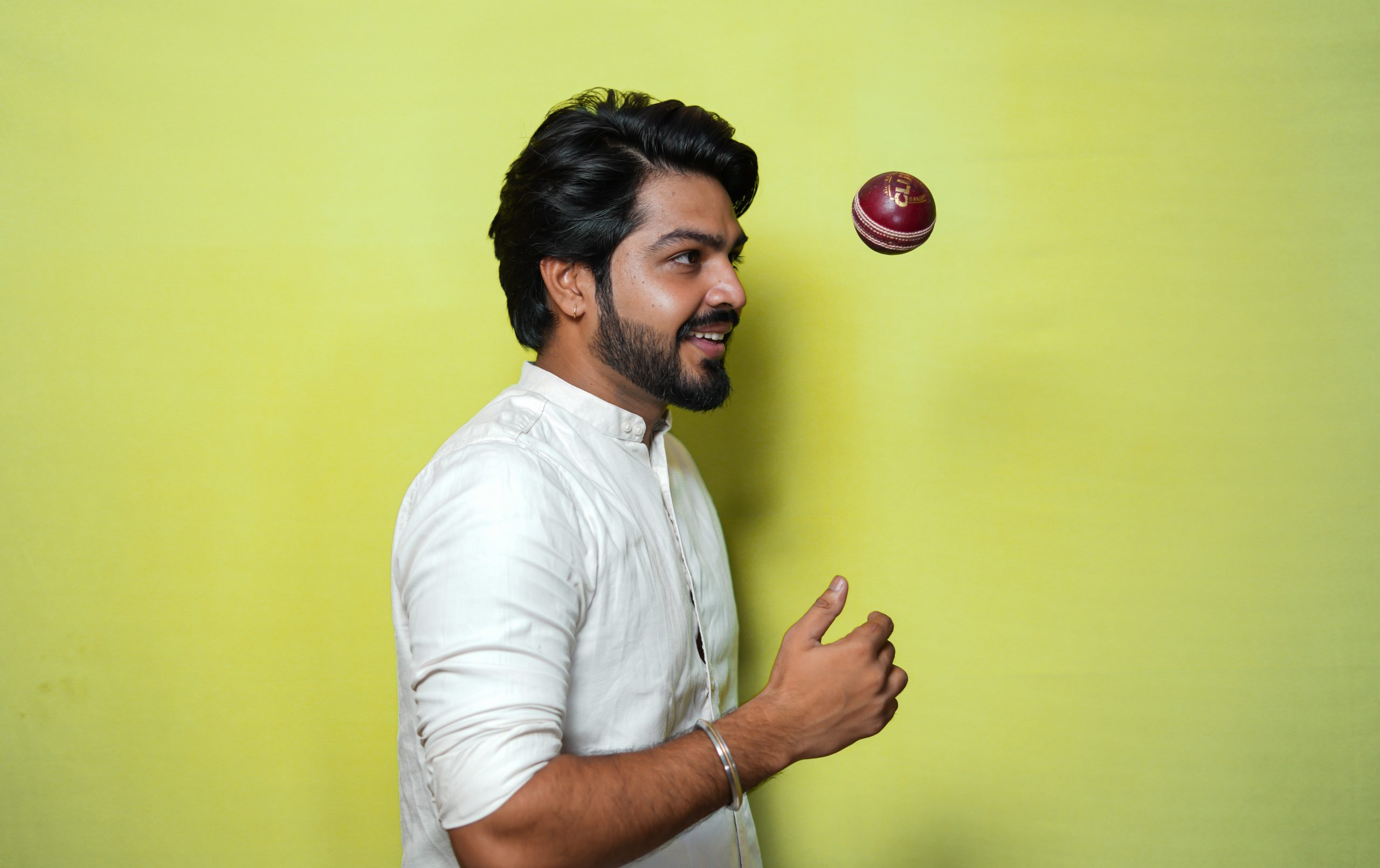 Handsome Man playing with cricket ball