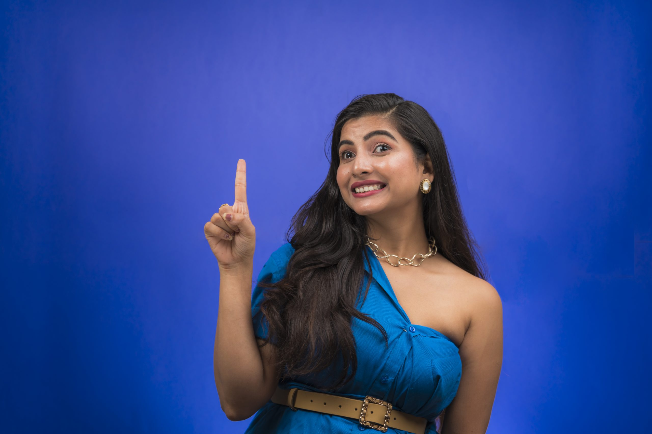 Happy Indian girl pointing up