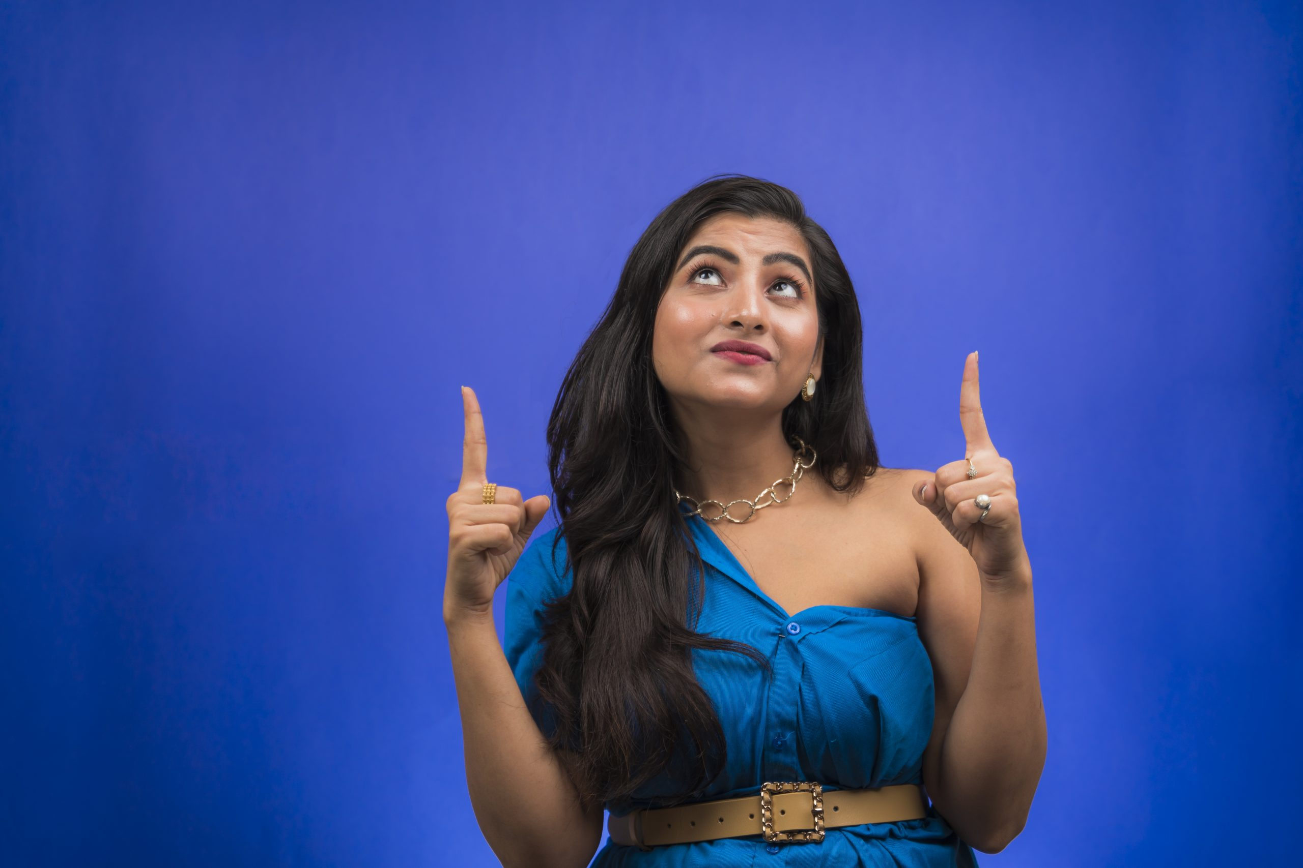 Happy indian girl pointing up both hands