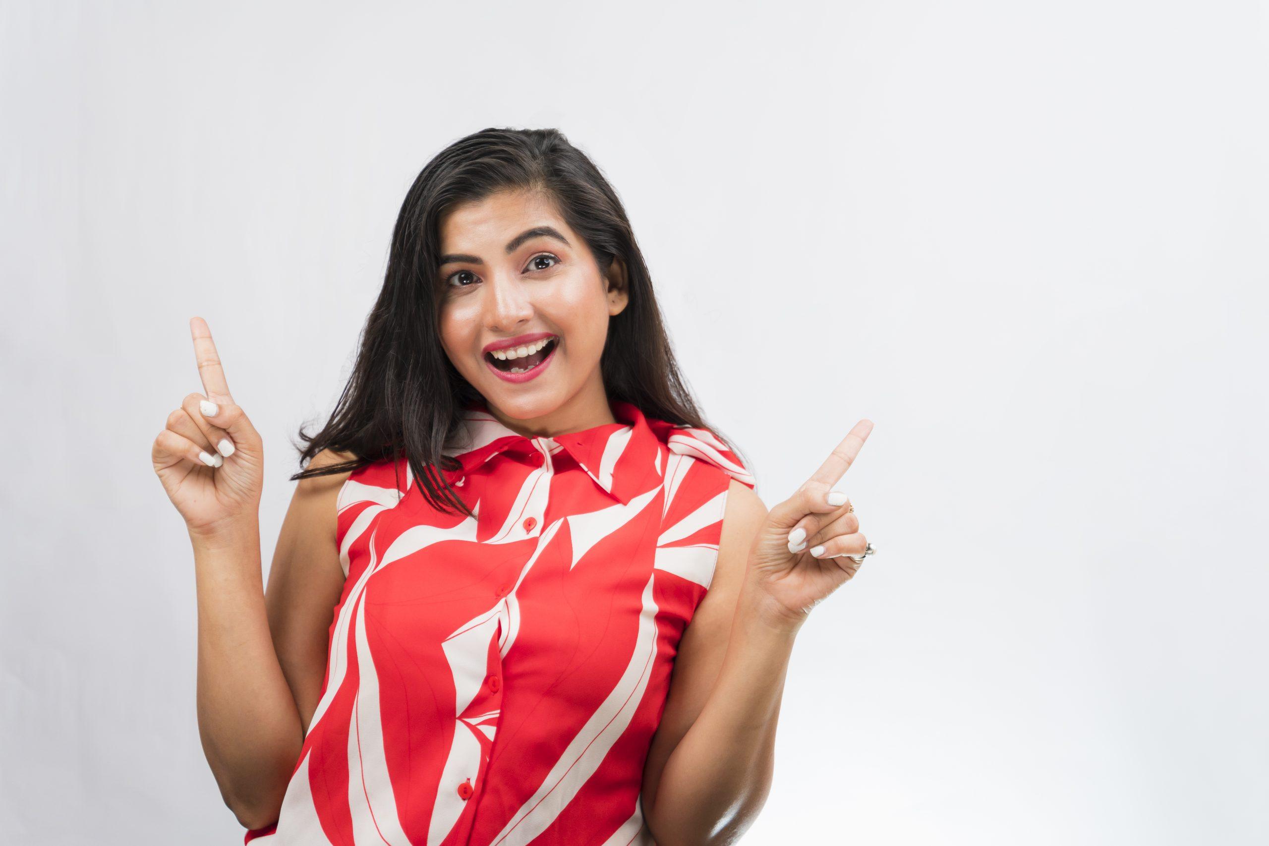 Happy Indian girl pointing upwards