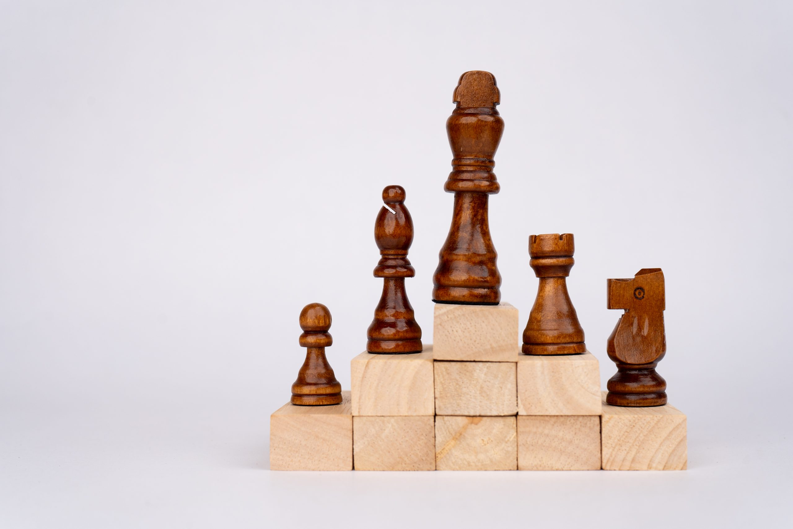 Black chess pieces on wooden blocks