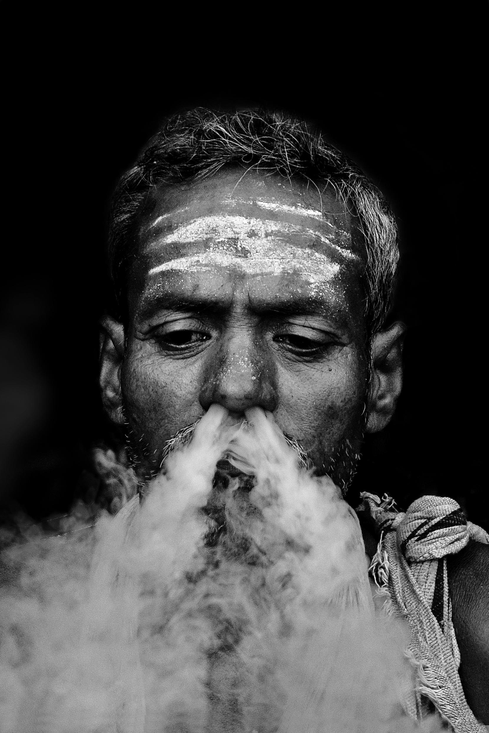 A sadhu smoking on the street.