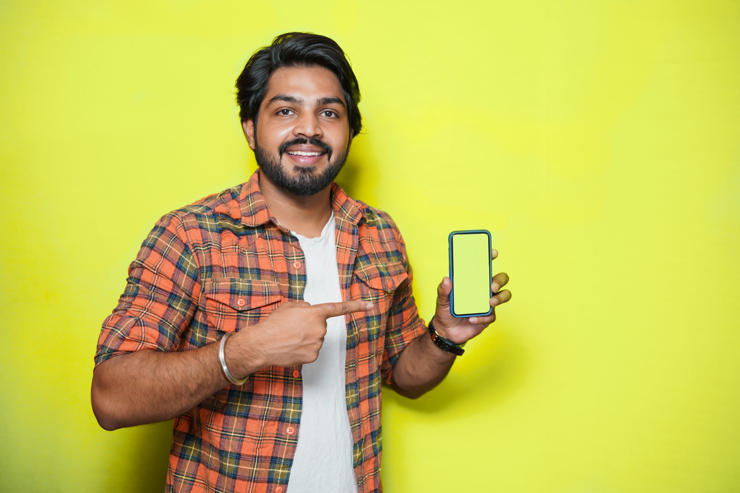 Indian male model pointing at cell phone