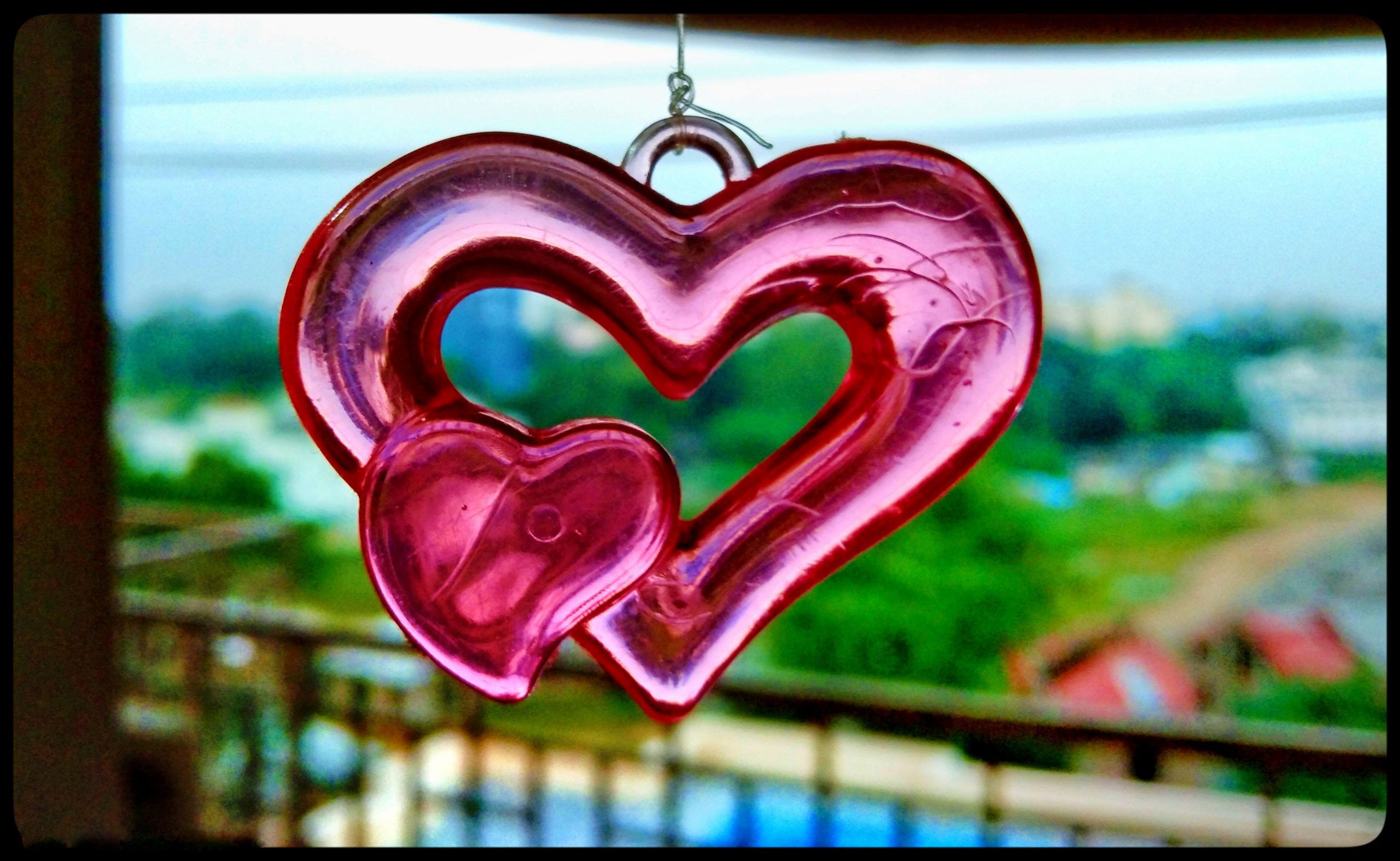 Pink plastic heart hanging from a string
