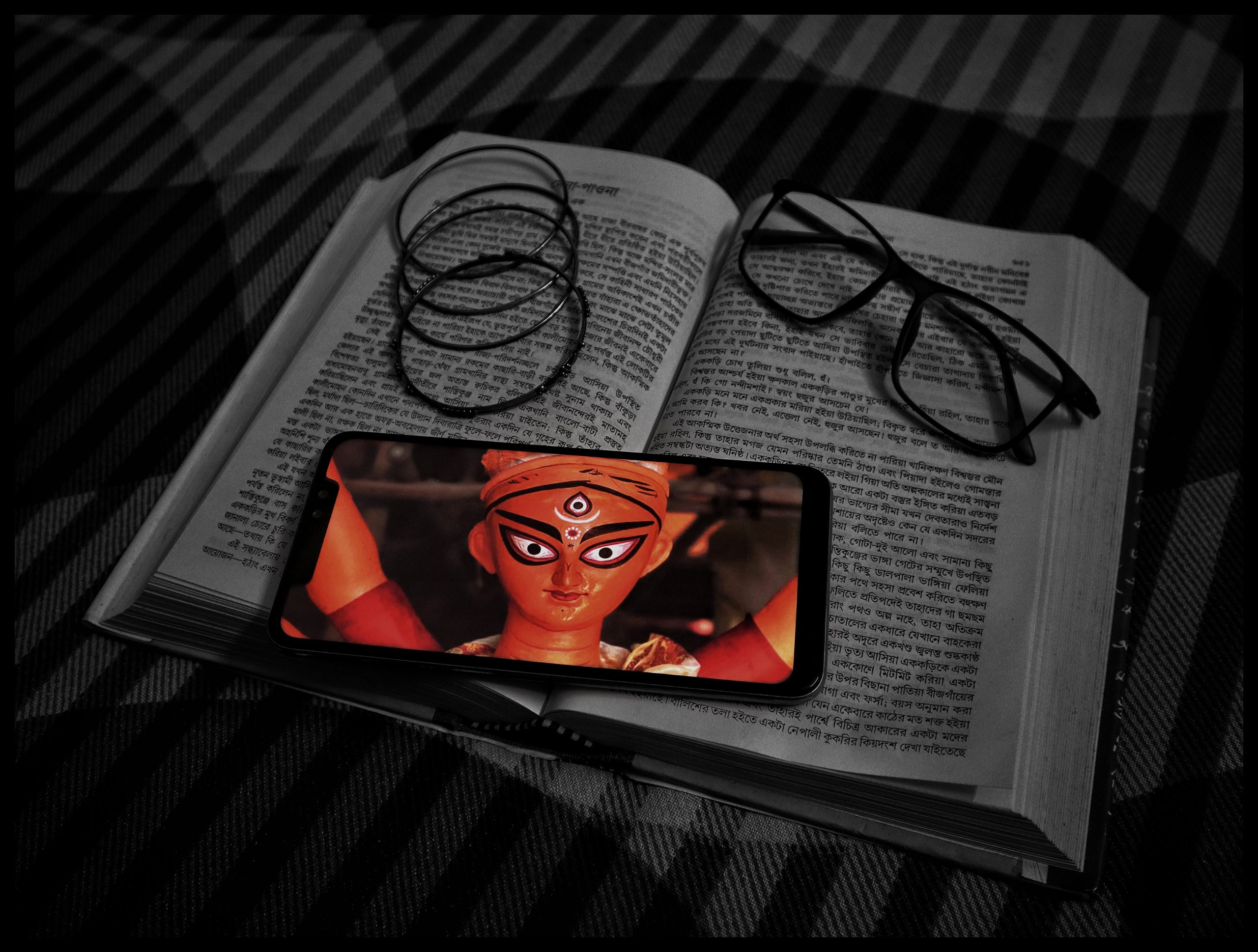 A smartphone with a picture of Ma Durga on it.