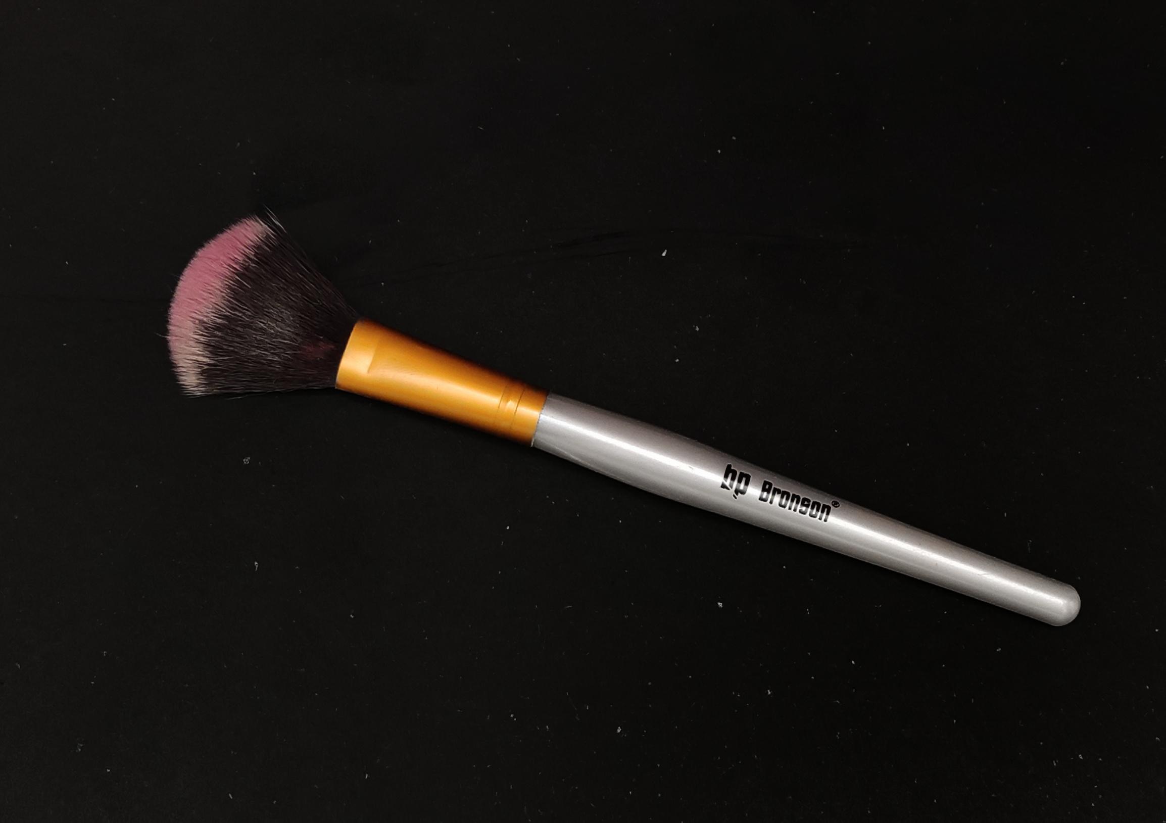 Makeup brush on black ground.