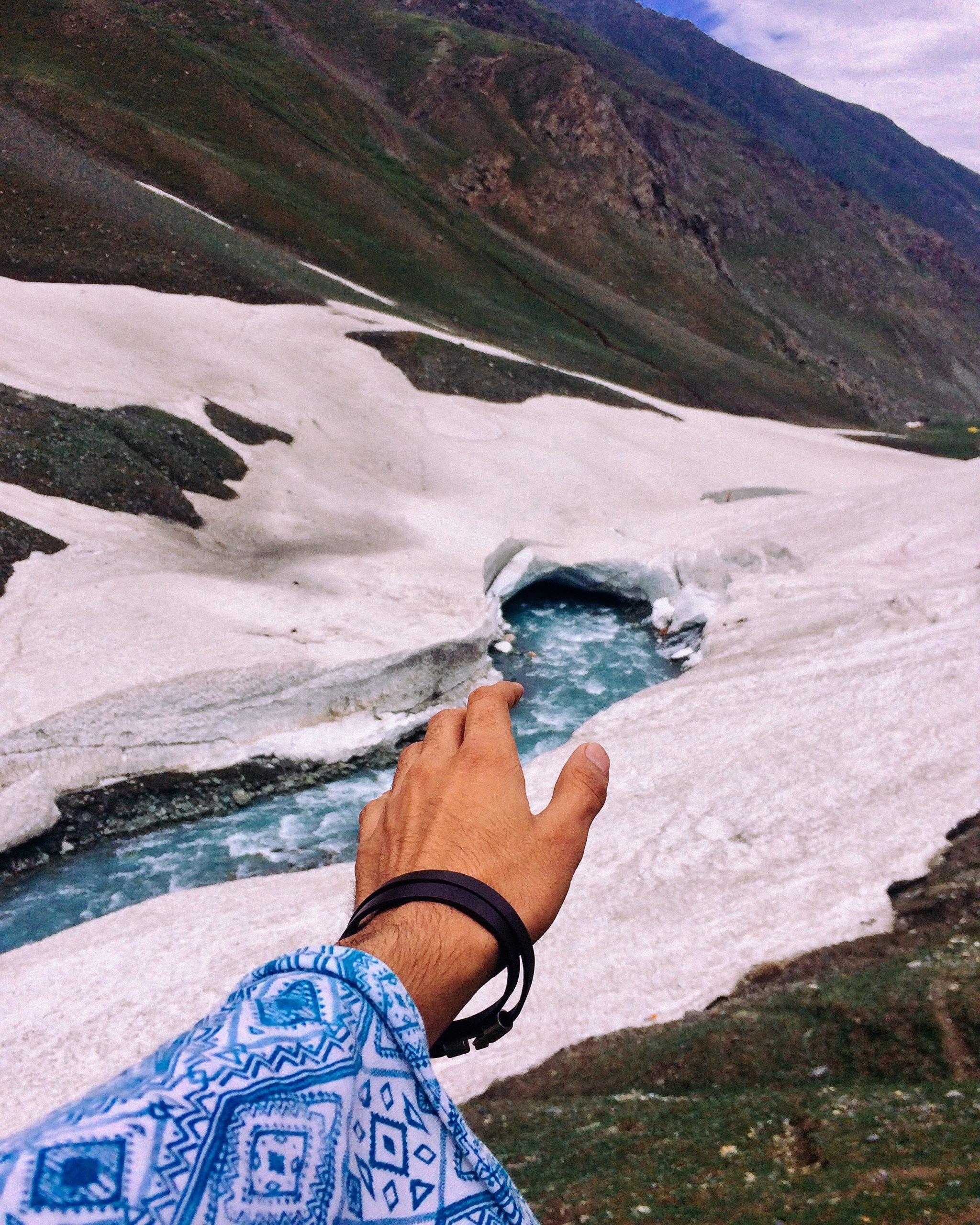 Male hand reaching towards mountain