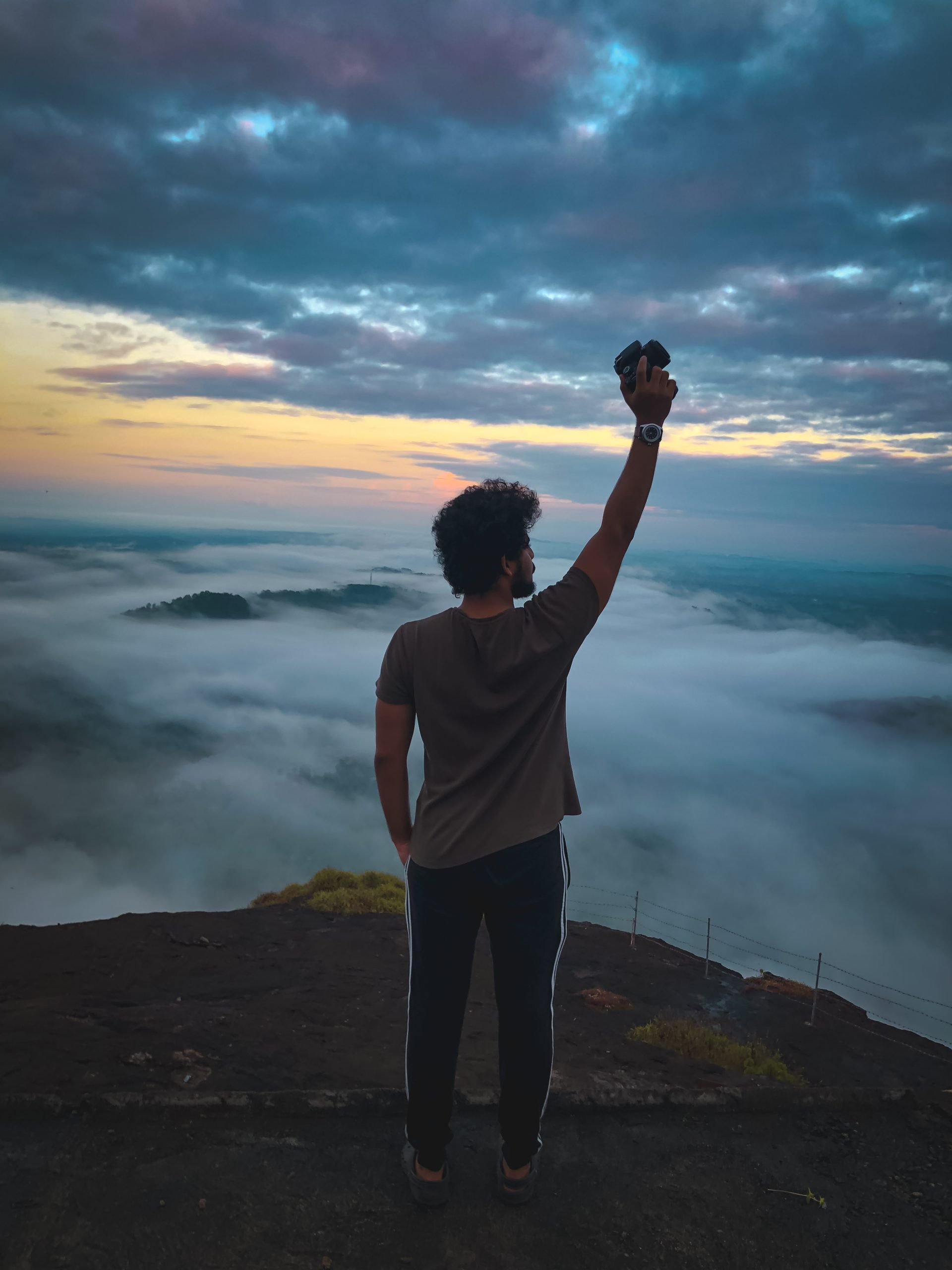 Man holding a camera at the peak