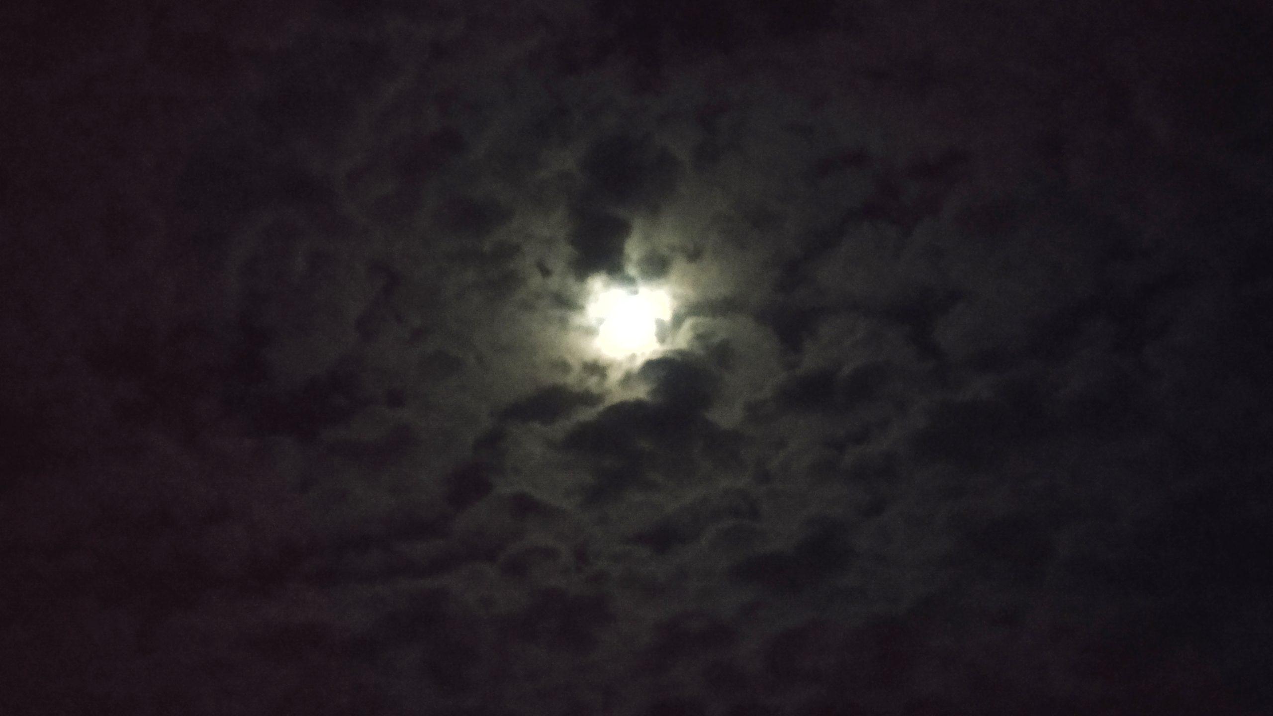 Moon between dark clouds