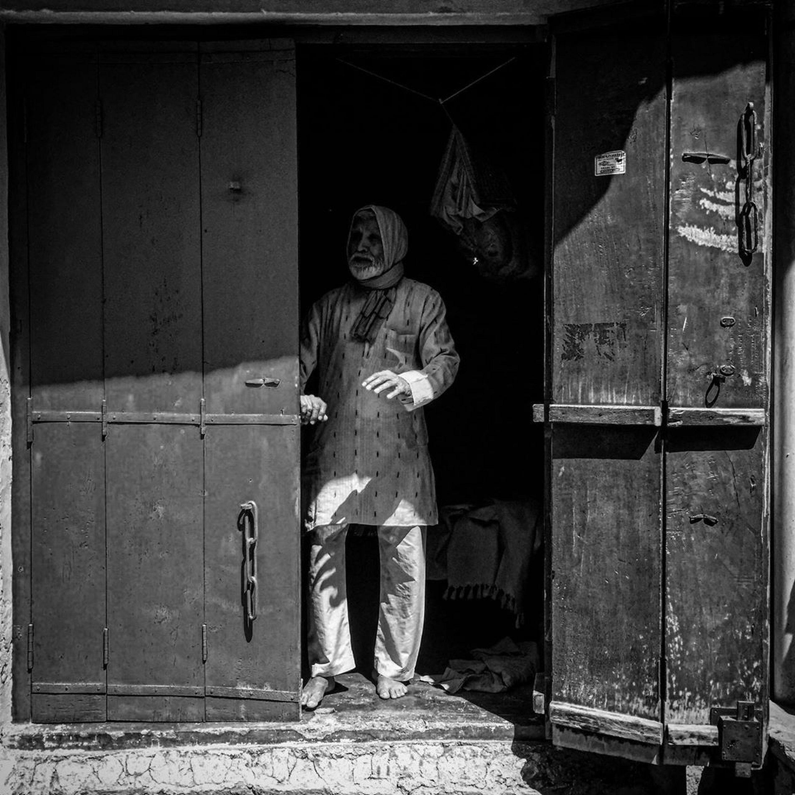 Old man standing at door