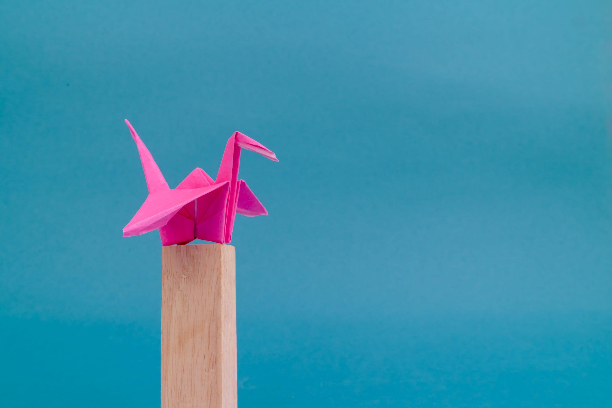 Origami crane on wooden block