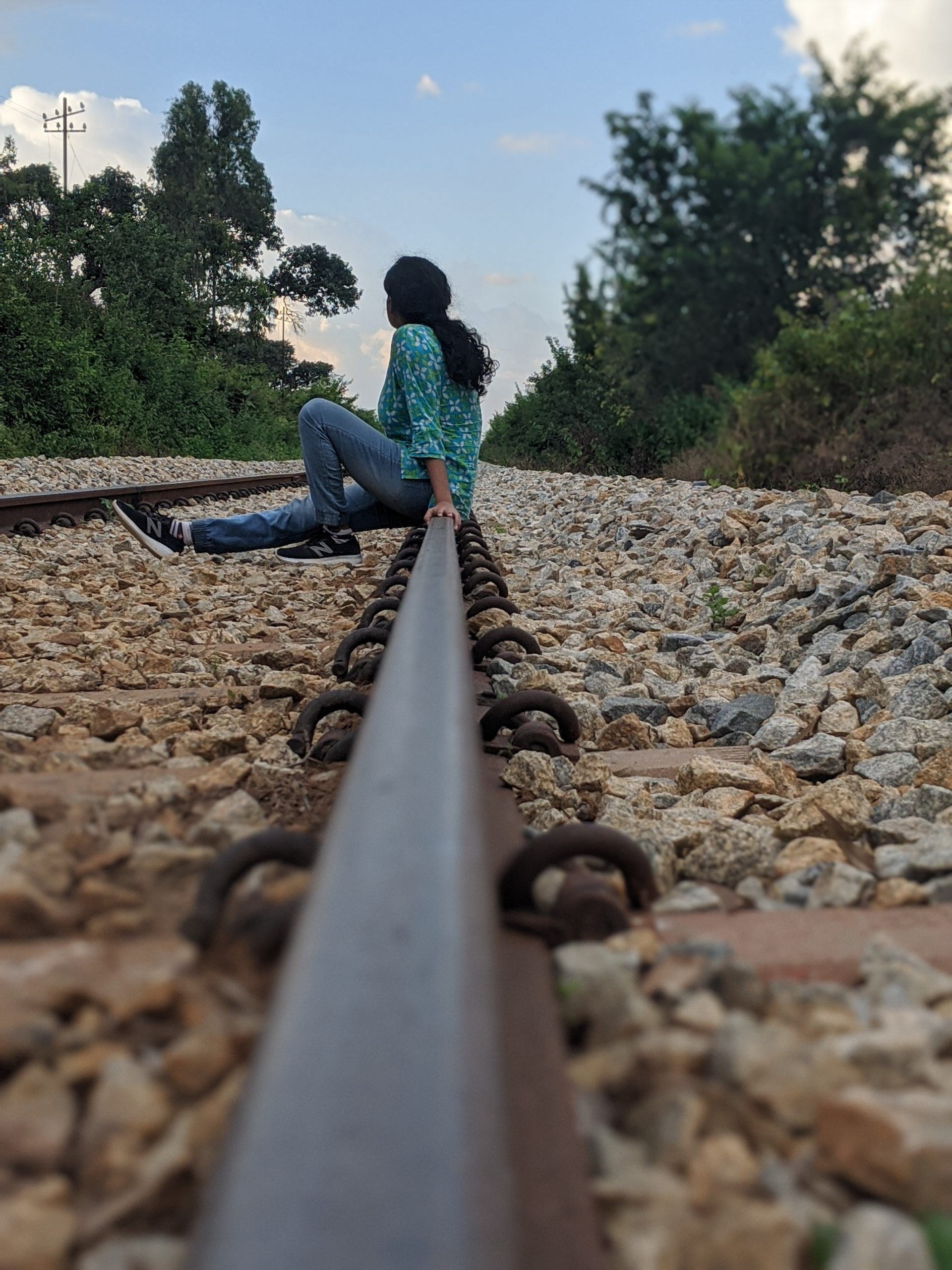 woman sitting on the railway track