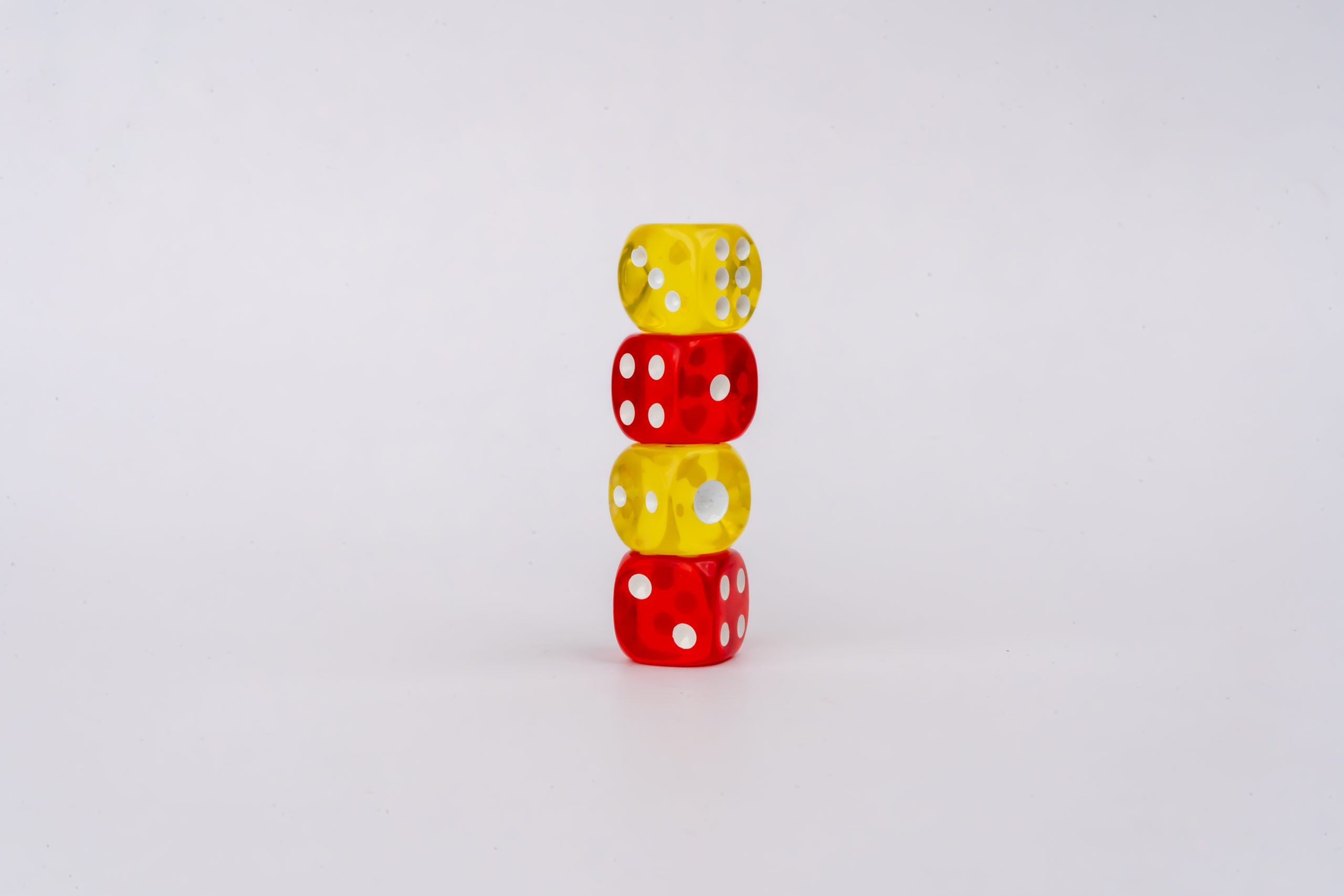 Red and yellow dice stack on white background