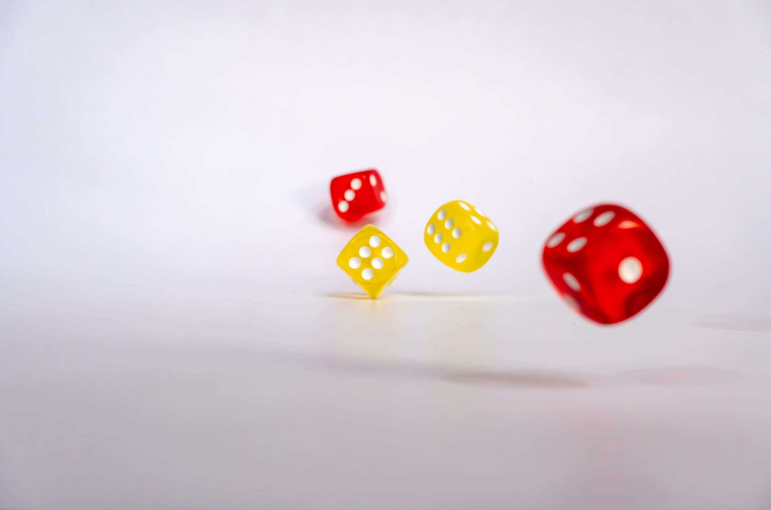 Red and yellow rolling dice on white background