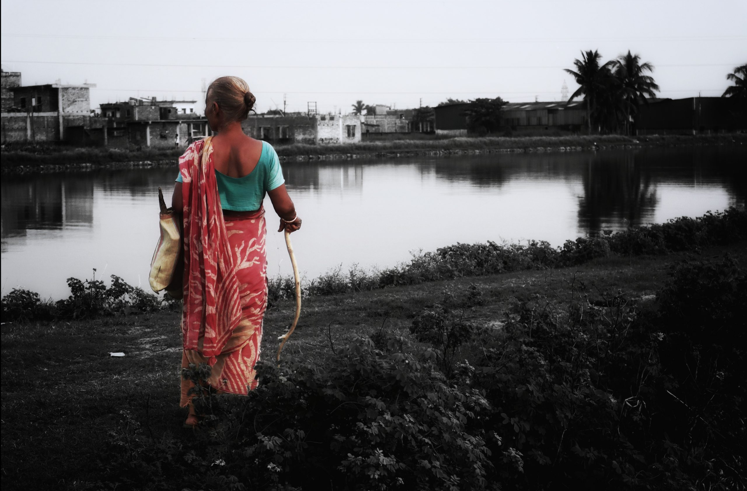A woman standing next to a pond