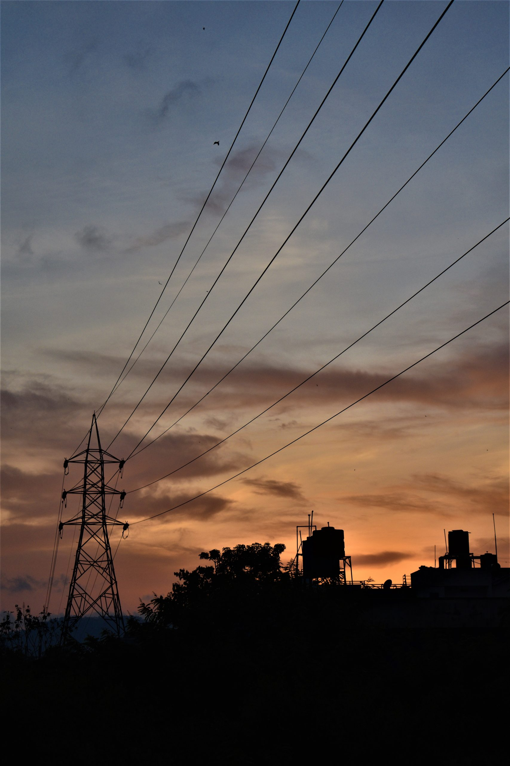 Sunset sky with silhouette of power tower