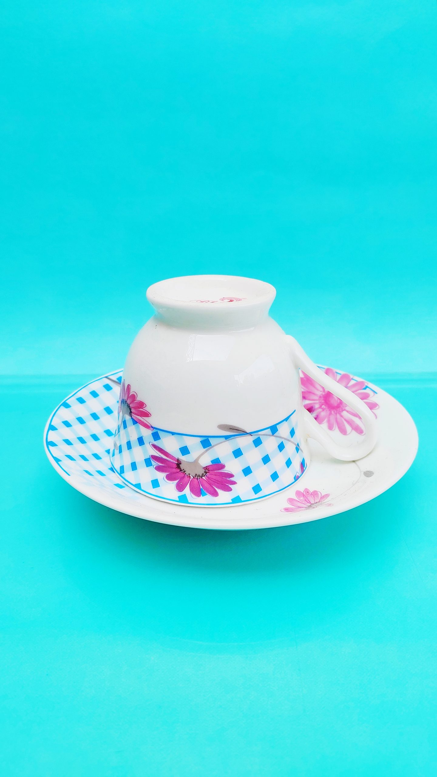 Teacup with plate on bright blue background