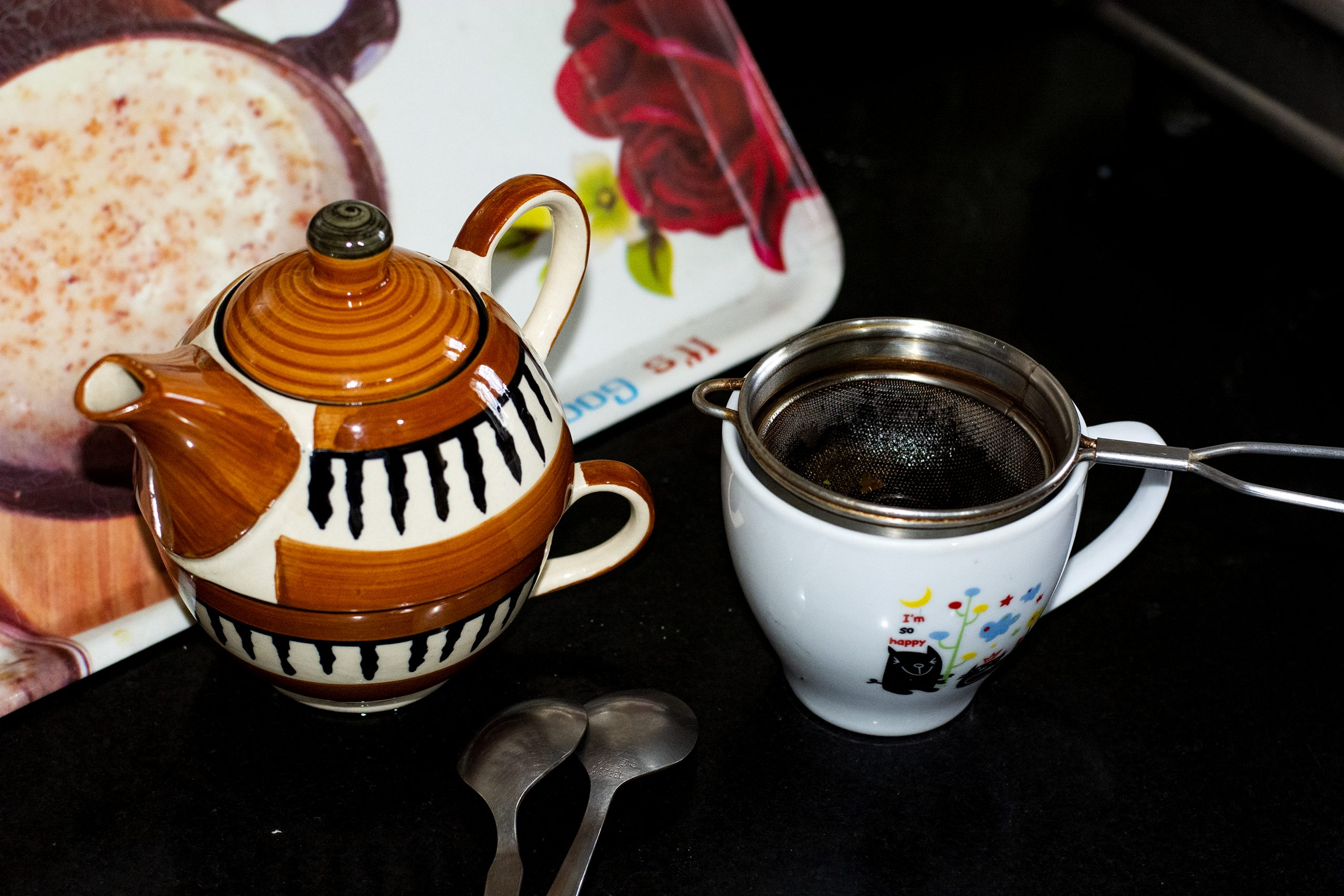 Teapot and cup with a strainer