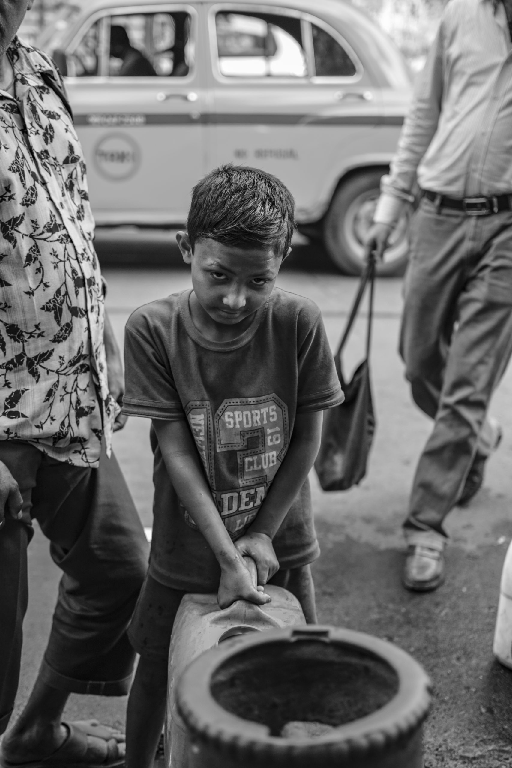 A small boy trying to lift a can of water.