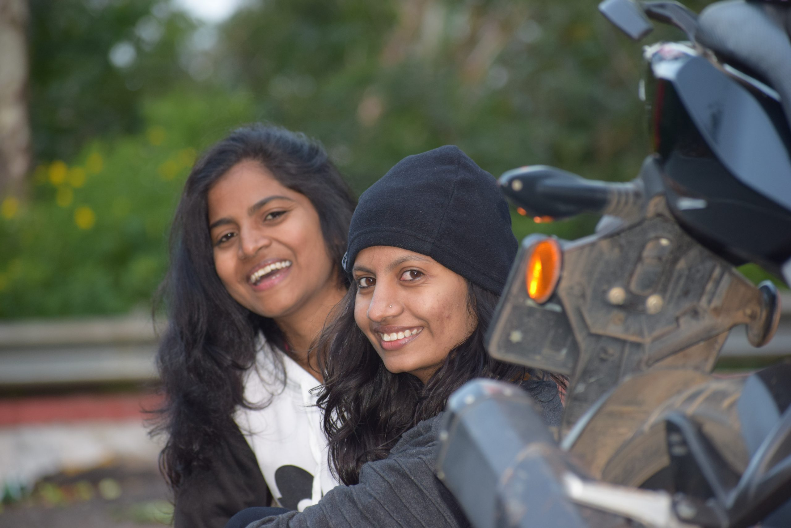 Two girls posing with a bike