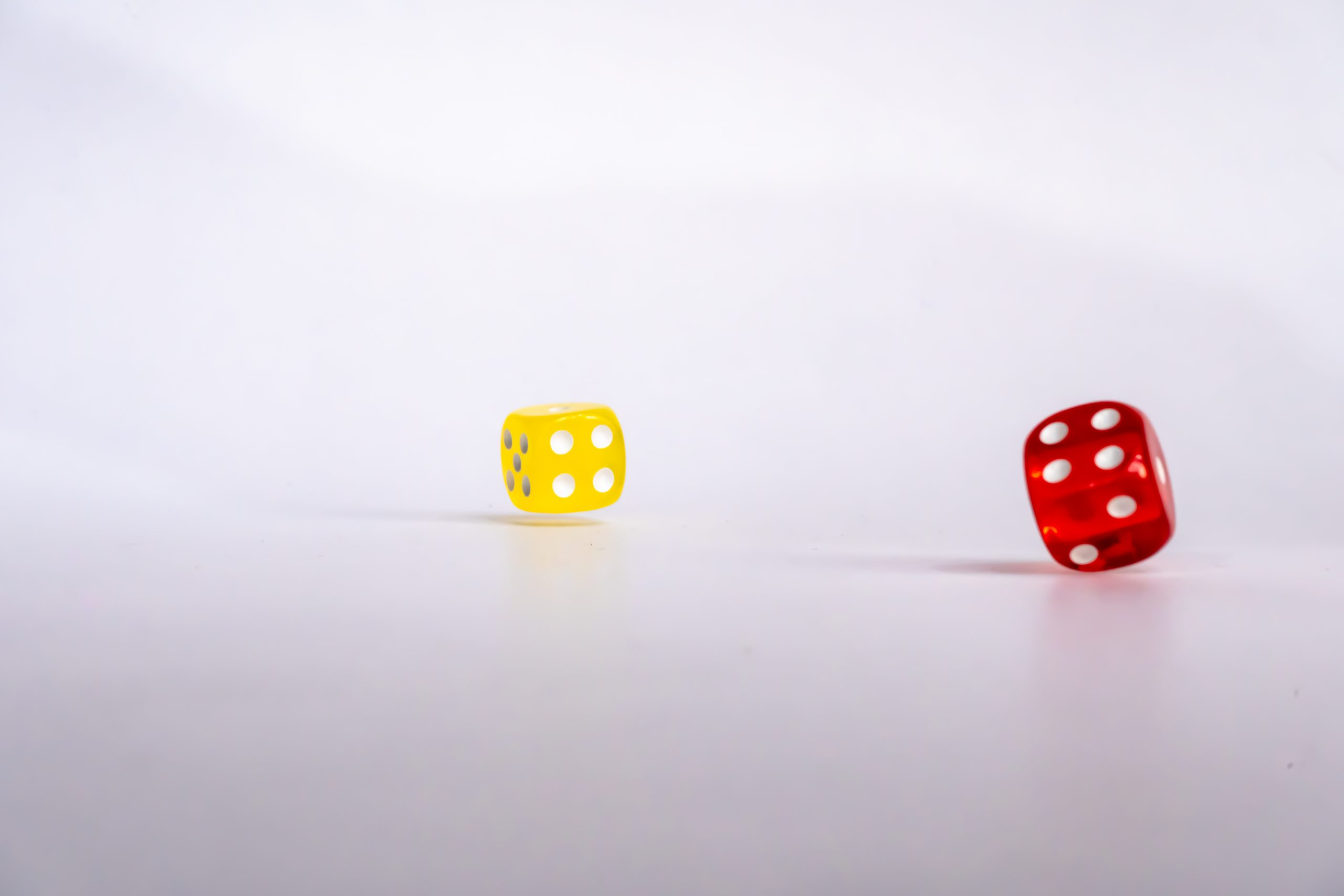 Two Rolling colored dice isolated on white