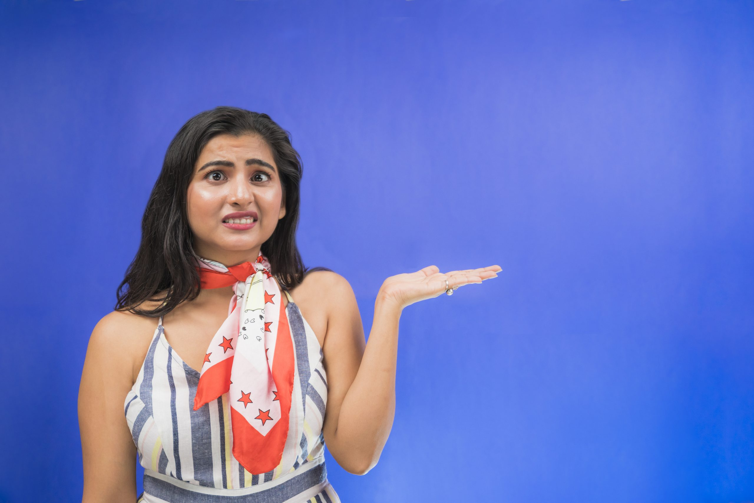 Unhappy Indian girl pointing hand sideways