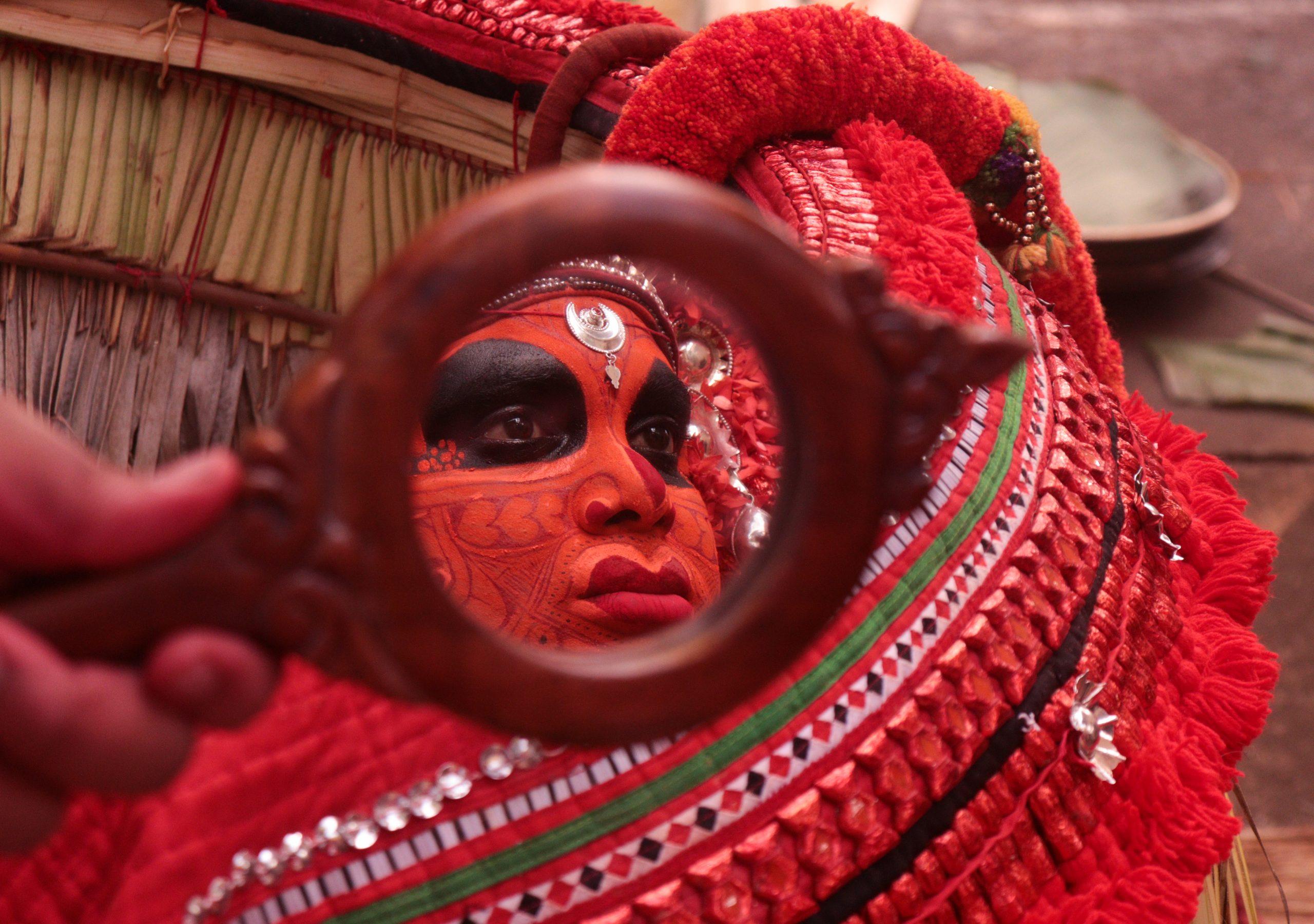 Vishnumoorthy Theyyam face makeup reflected in mirror