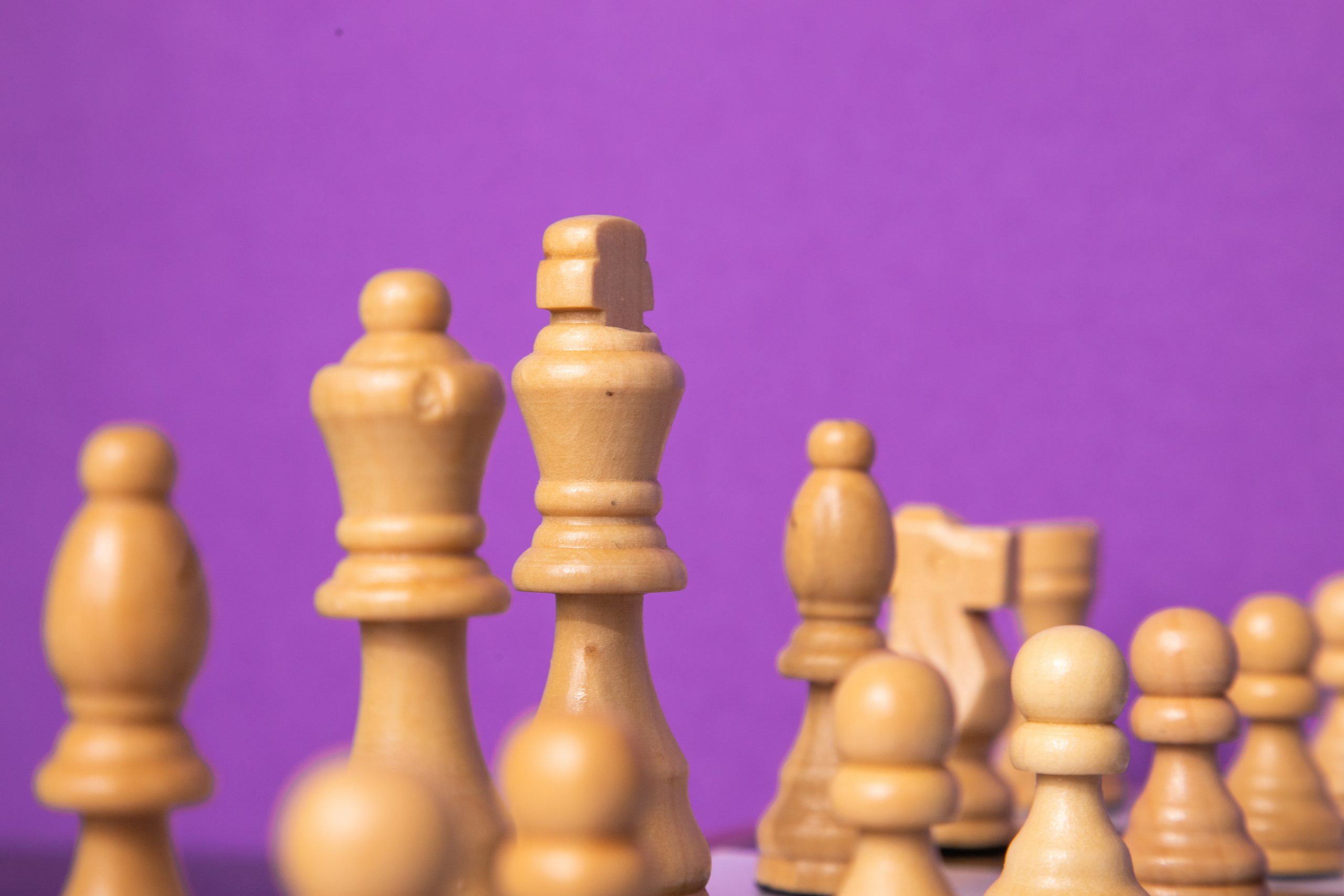 White chess pieces on purple background