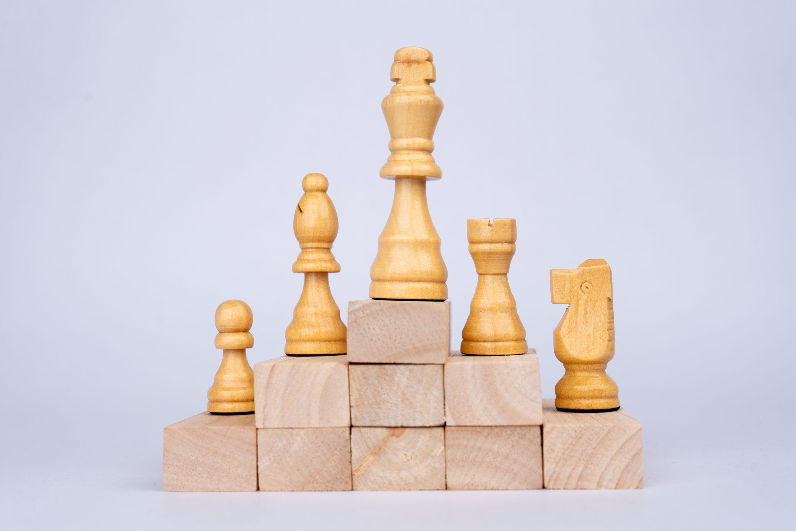 White chess pieces on wooden blocks