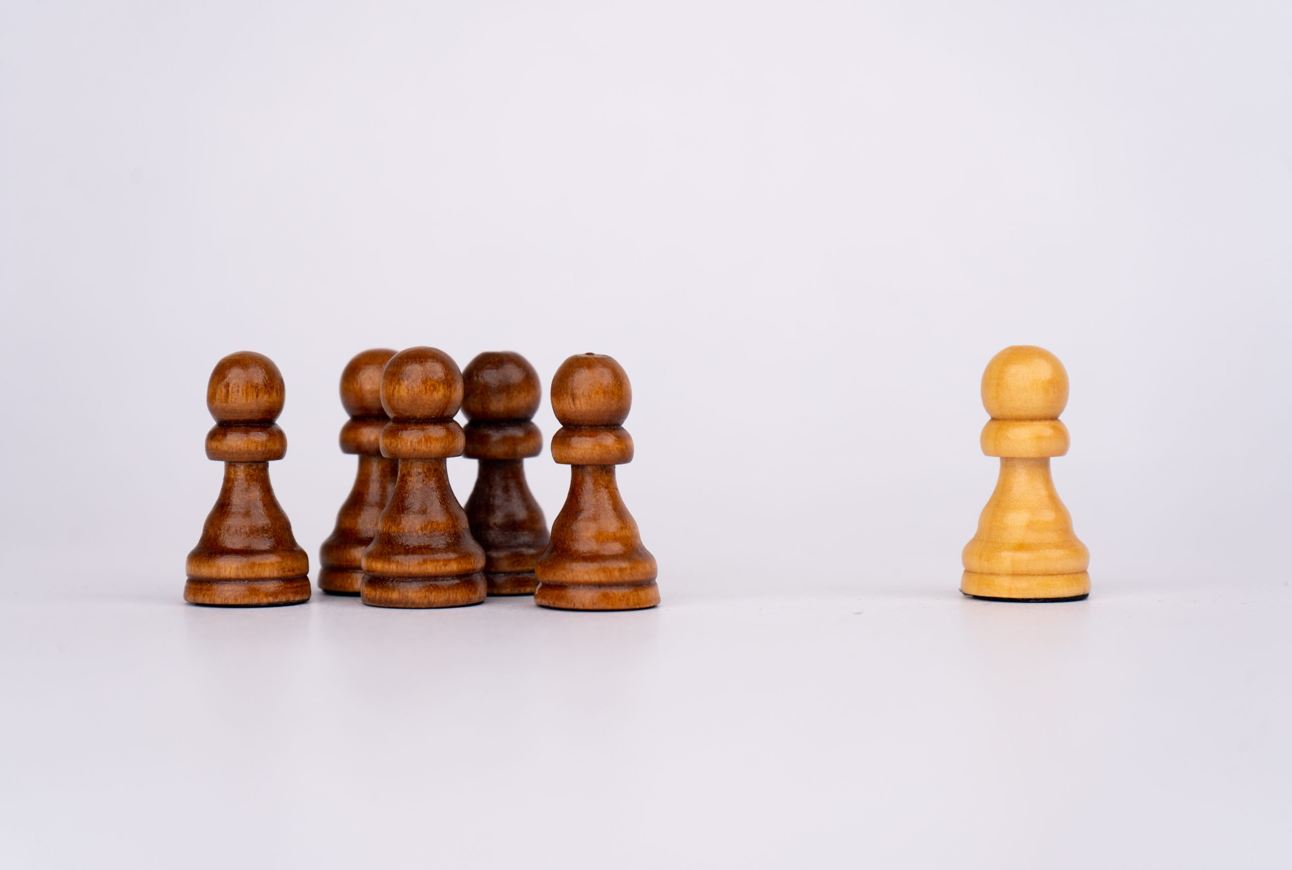 White pawn stands against crowd of black pawns