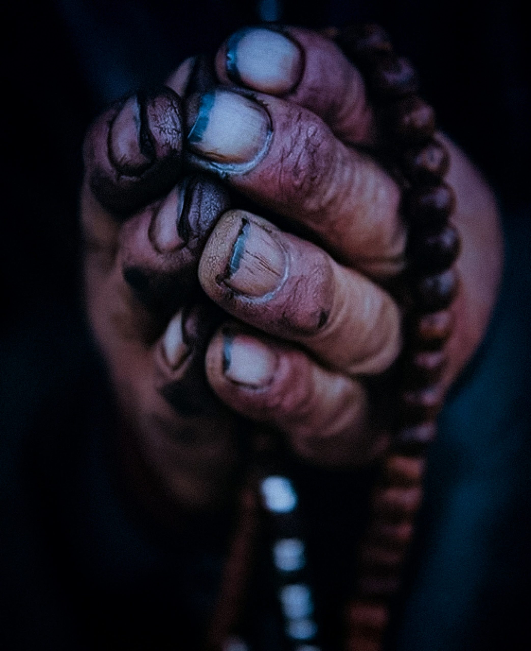 Worn out praying hands with rosary