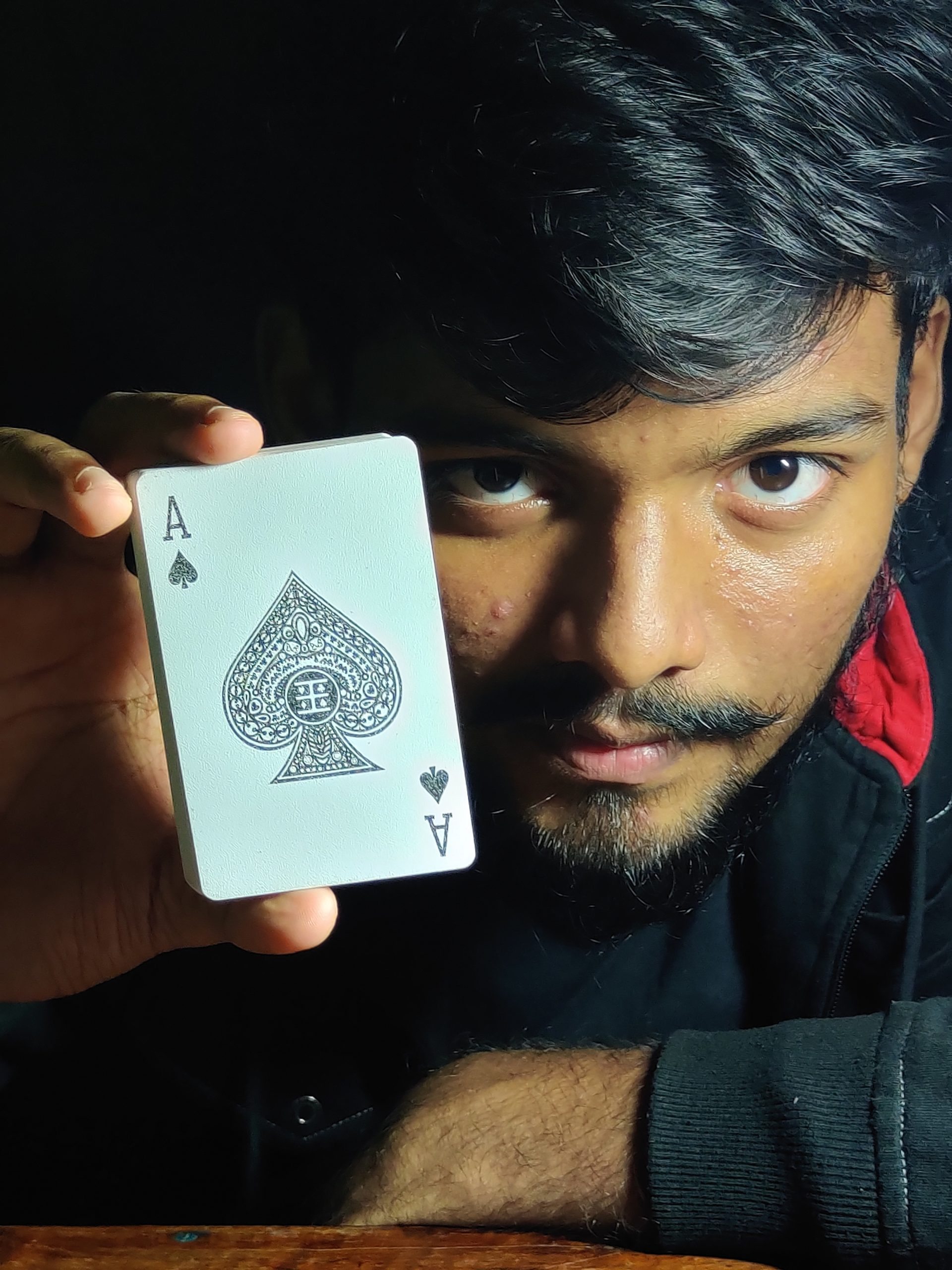 Young indian male holding deck of cards