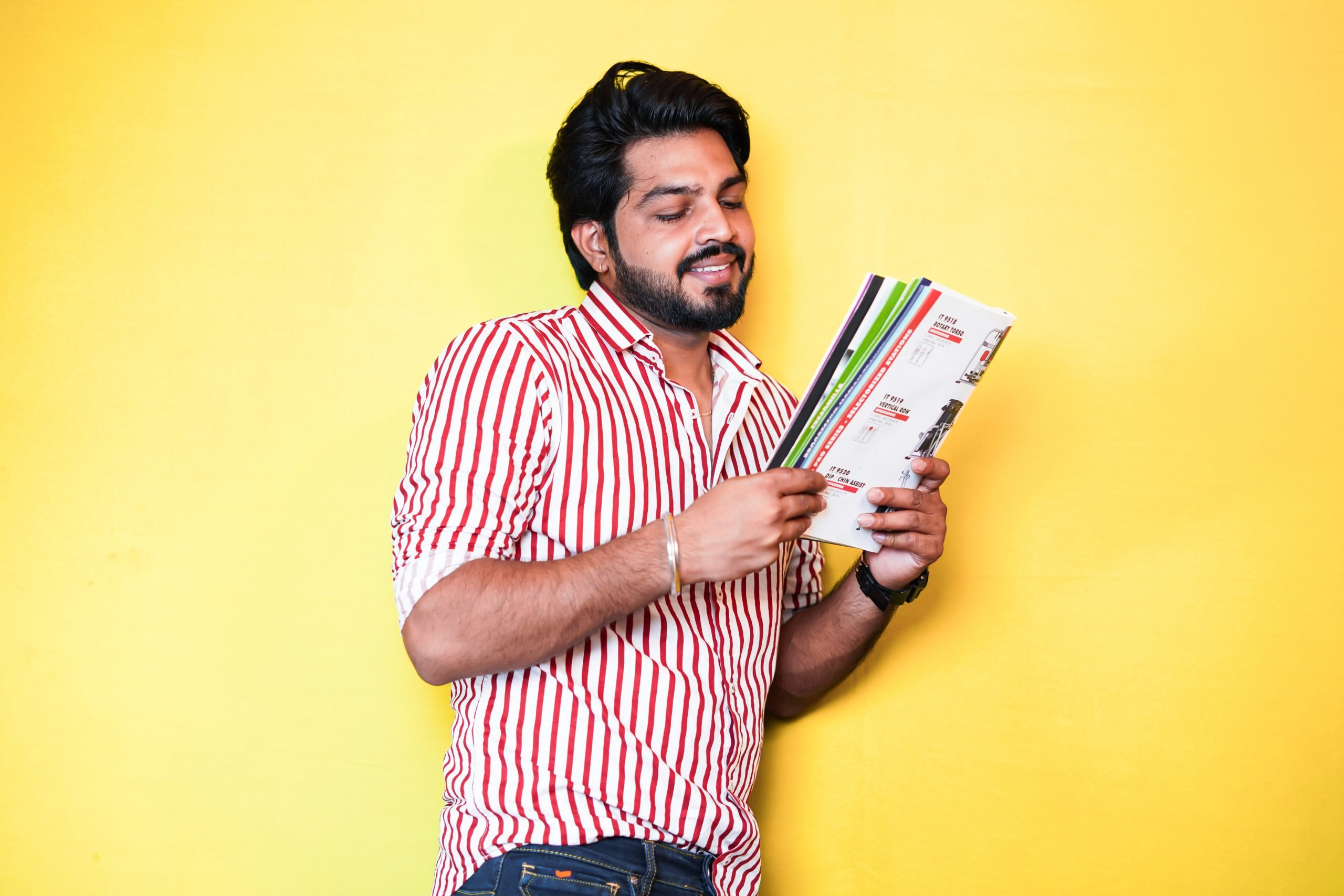 Young indian man leaning against wall reading book